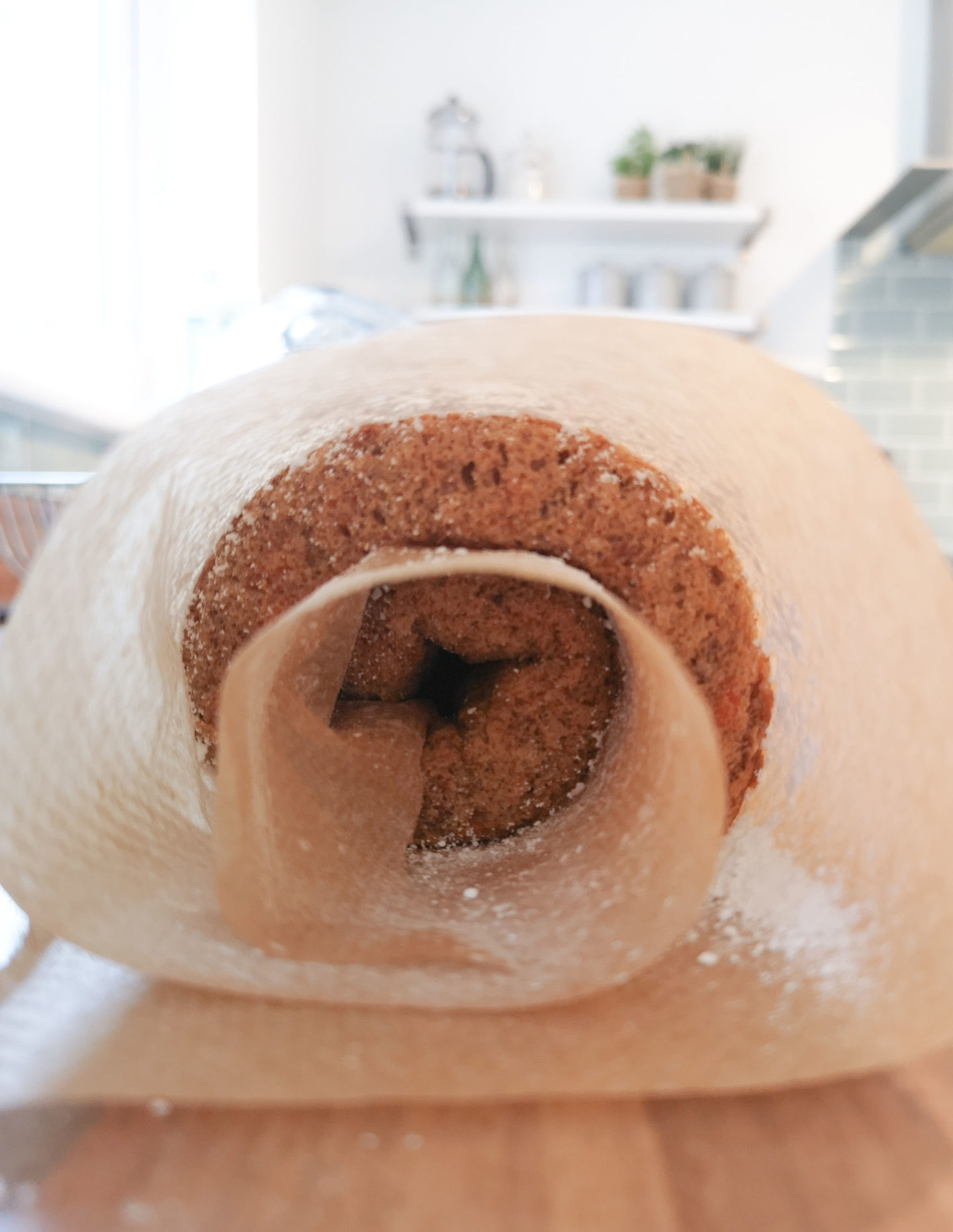 Carrot cake Swiss roll rolled up in baking paper