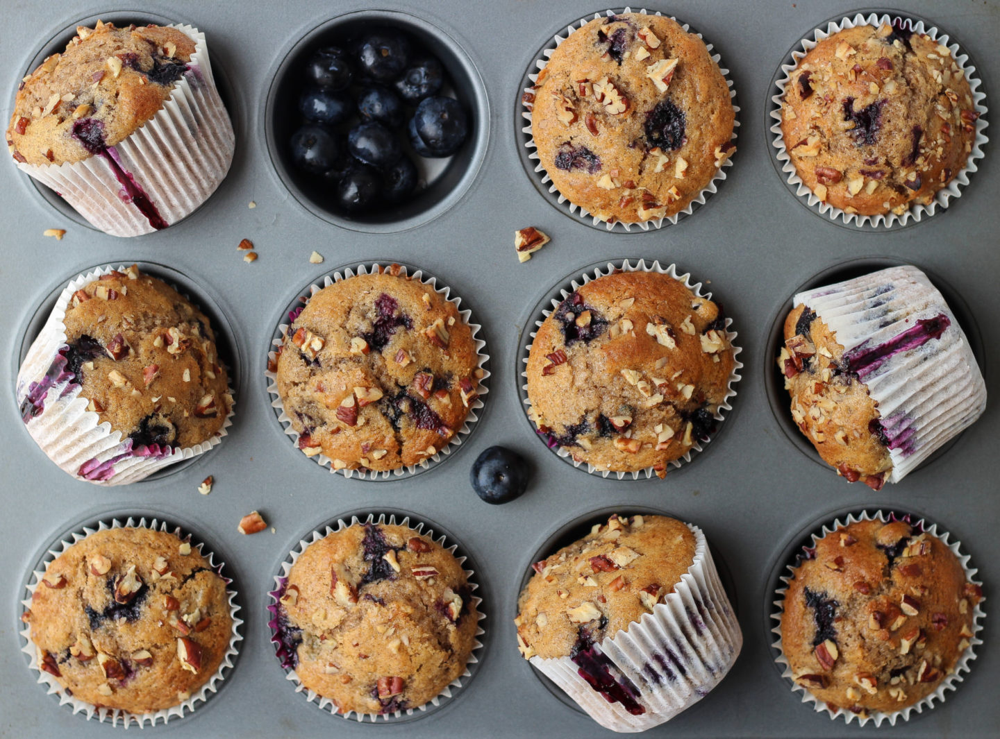 Muffin tray filled with blueberry nut muffins and blueberries