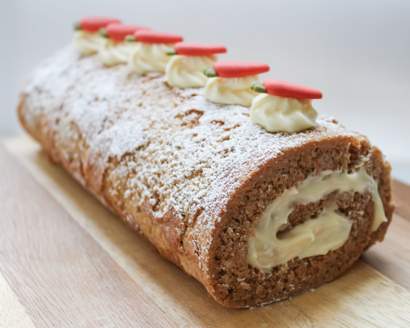Fully decorated carrot cake Swiss roll with cream cheese frosting/icing