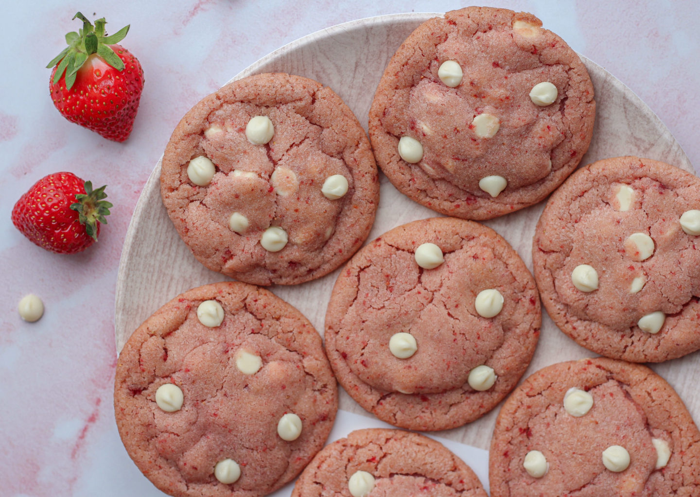 view from above of several strawberry white chocolate cookies on a small plate
