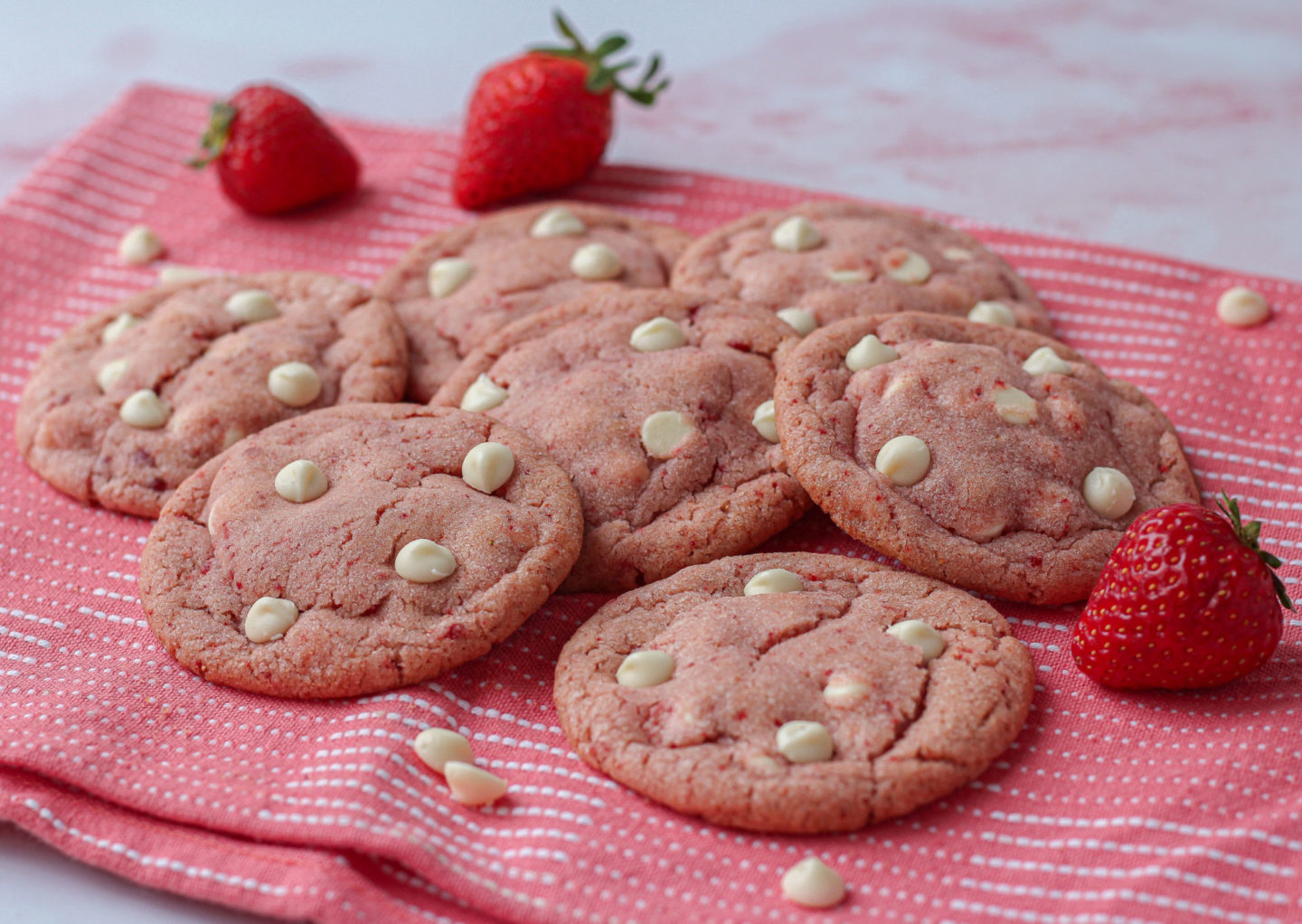Several strawberry white chocolate cookies on a pink tea towel