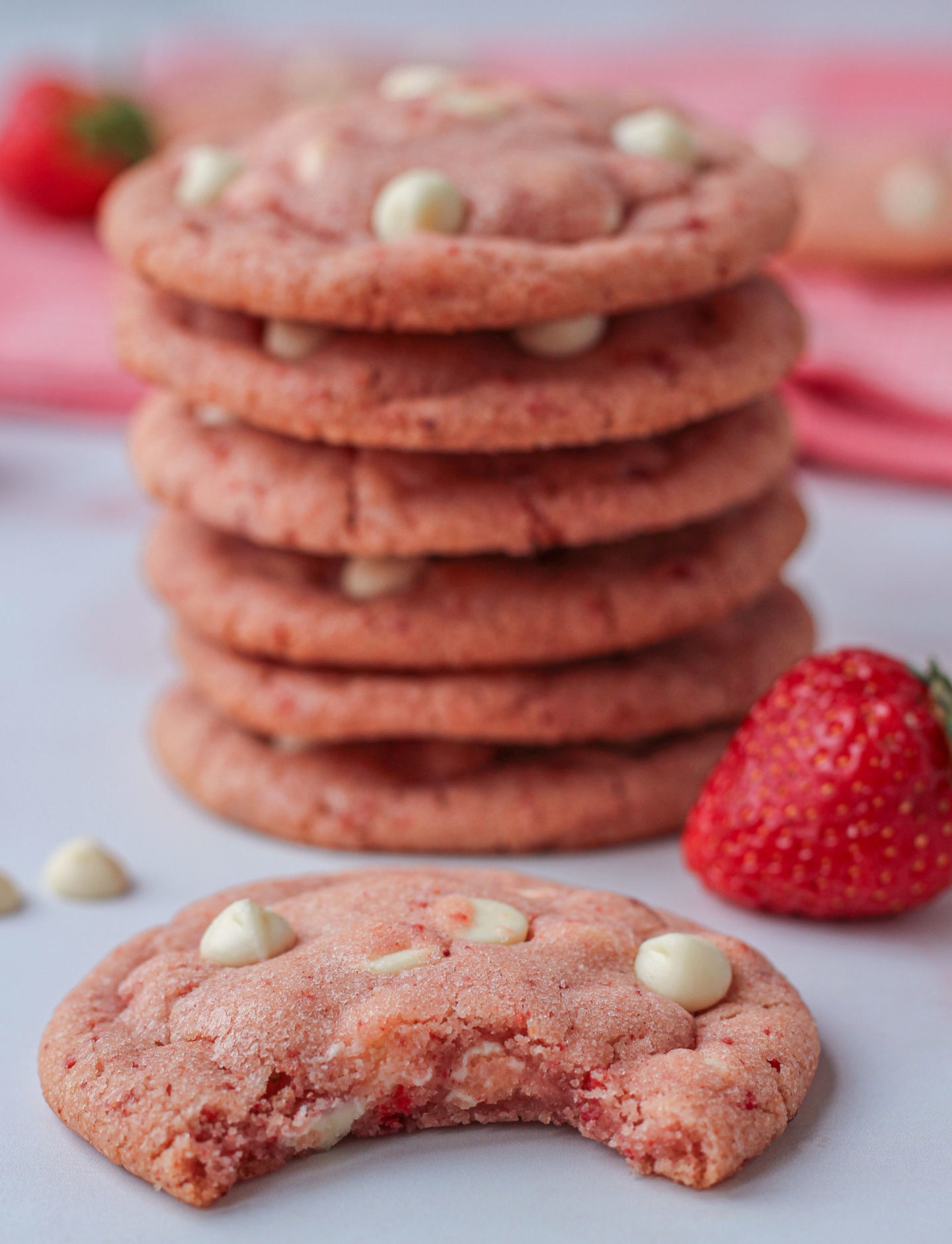 close up of a strawberry white chocolate cookie with bite taken out of it, with out of focus tower of cookies behind it