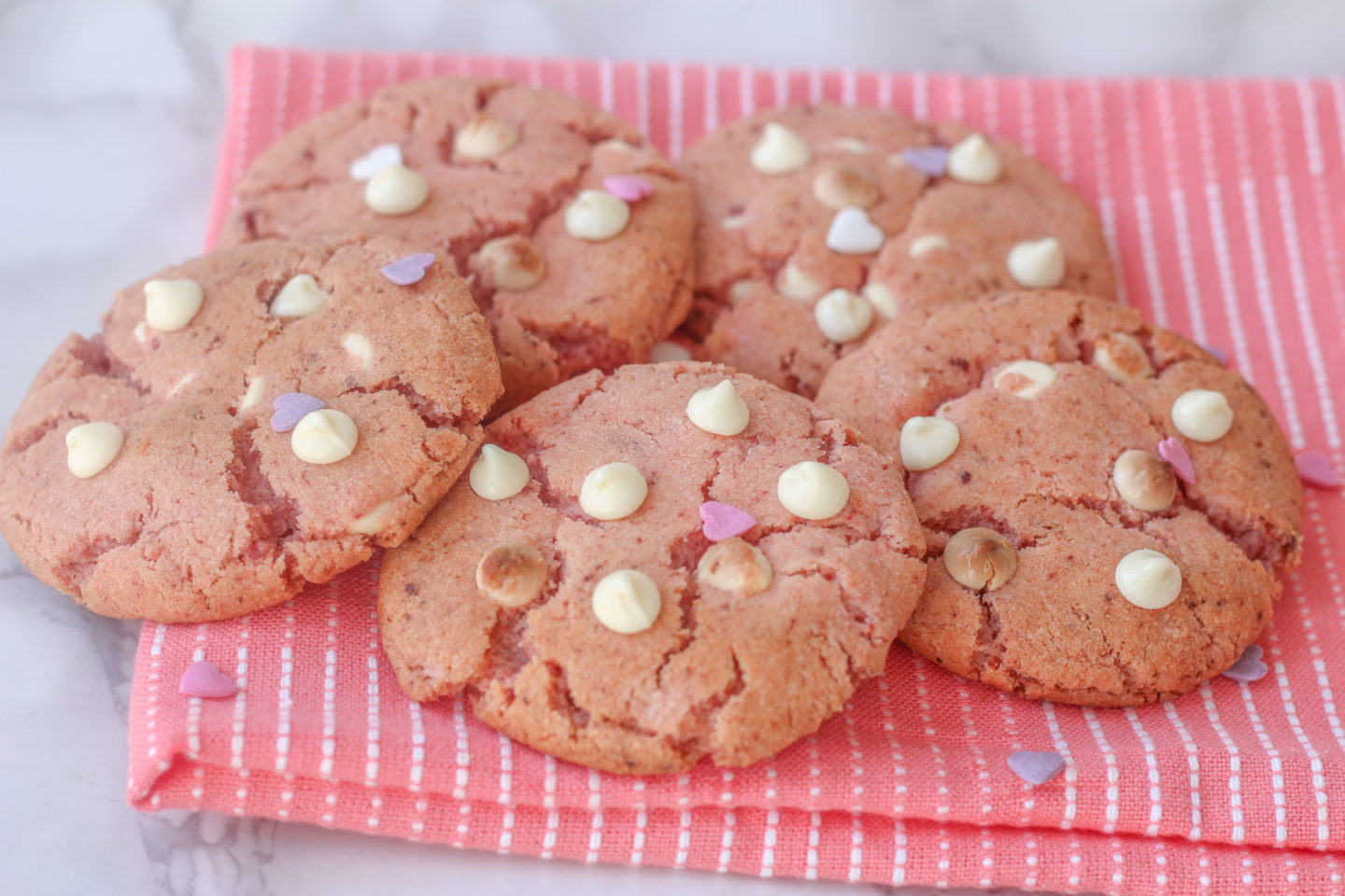 several strawberry white chocolate cookies on top of pink tea towel