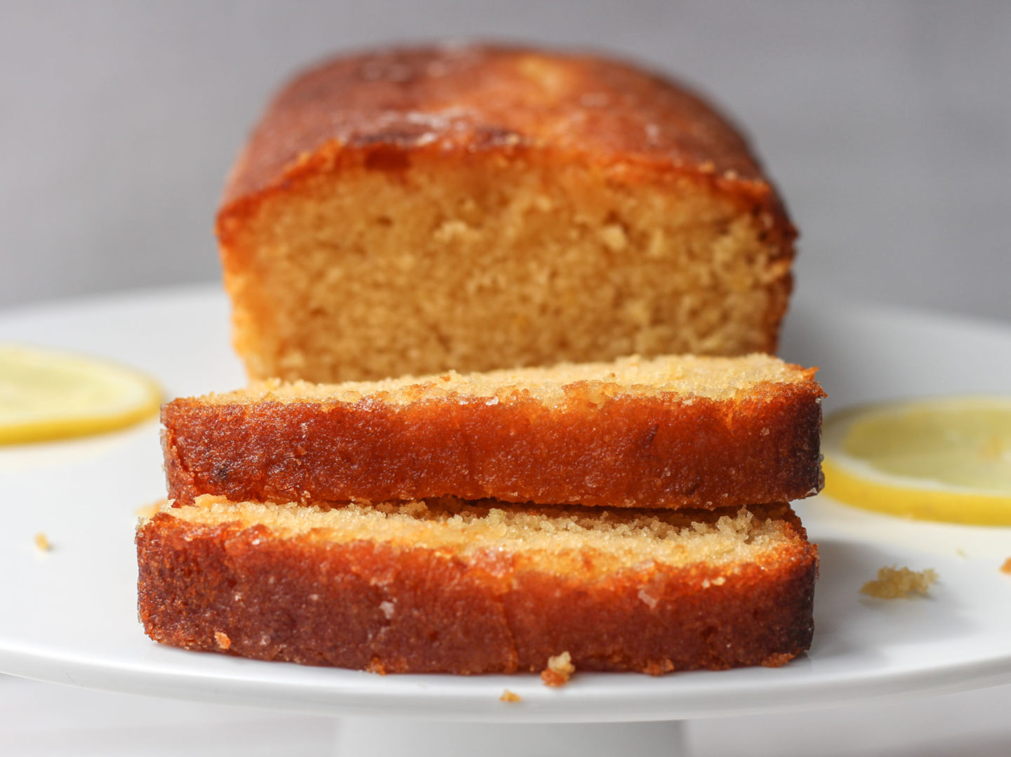 close up of slices of cake in front of lemon drizzle loaf cake