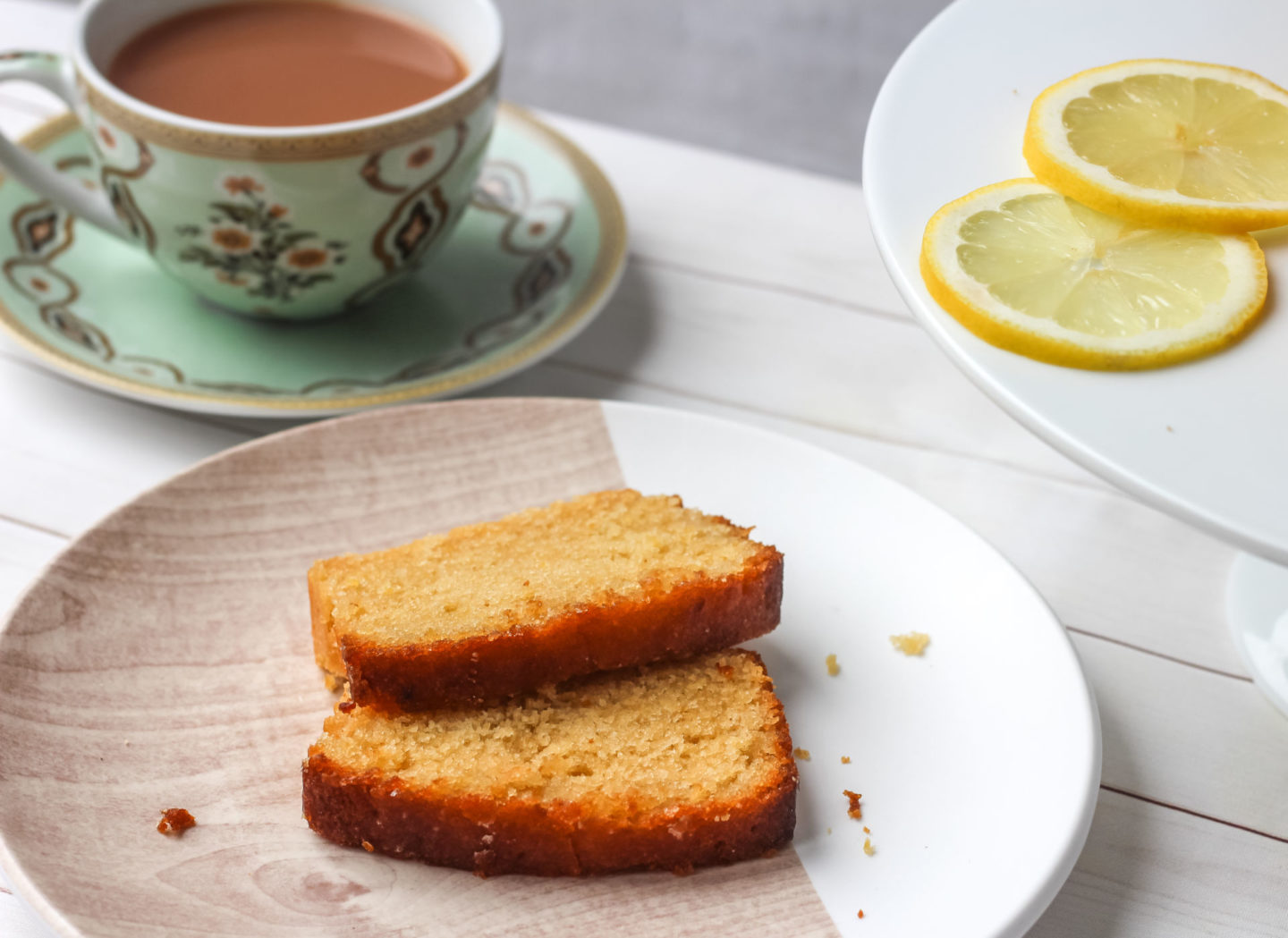 slices of lemon drizzle loaf cake with teacup and lemon slices