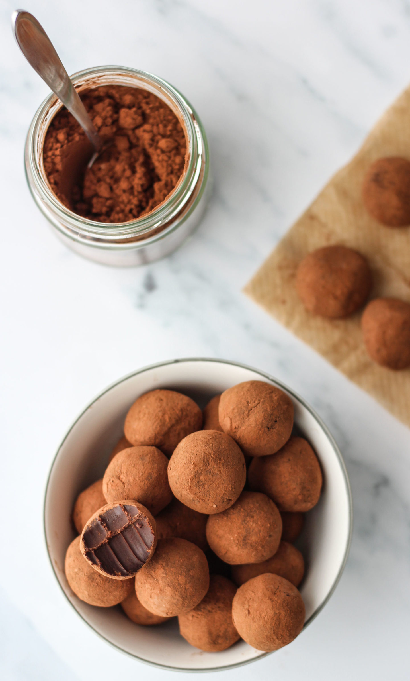 chocolate truffles in bowl and jar of cocoa powder
