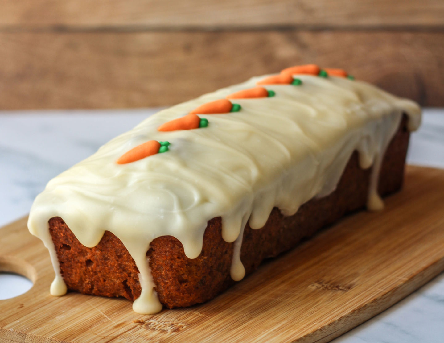 carrot loaf cake covered in cream cheese drip icing