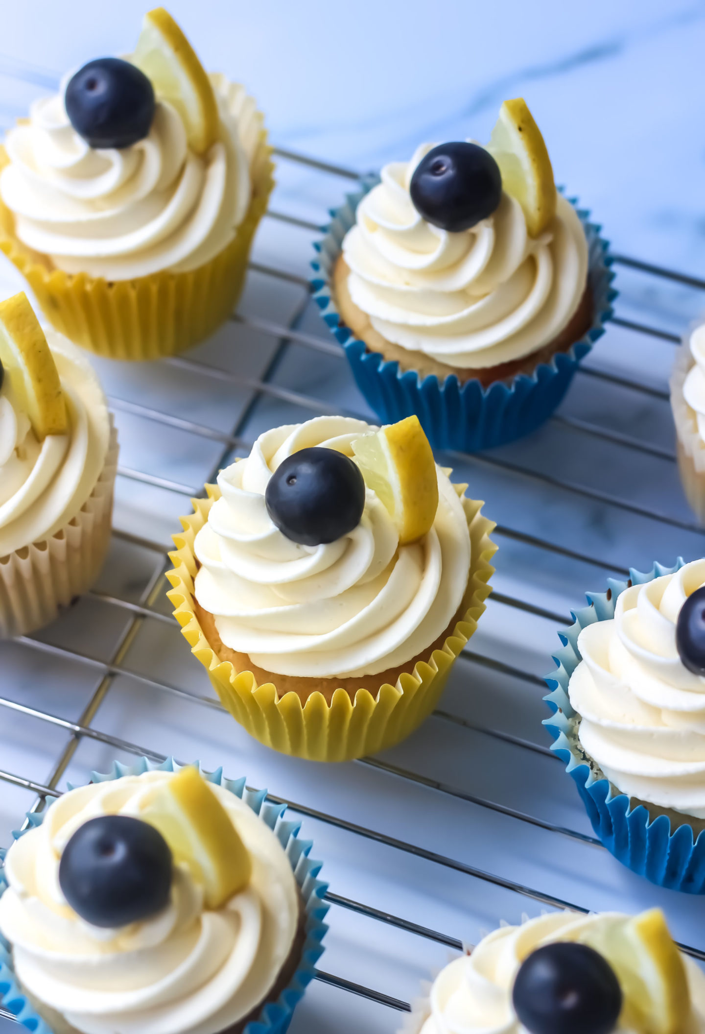 several decorated lemon blueberry cupcakes on a wire cooling rack