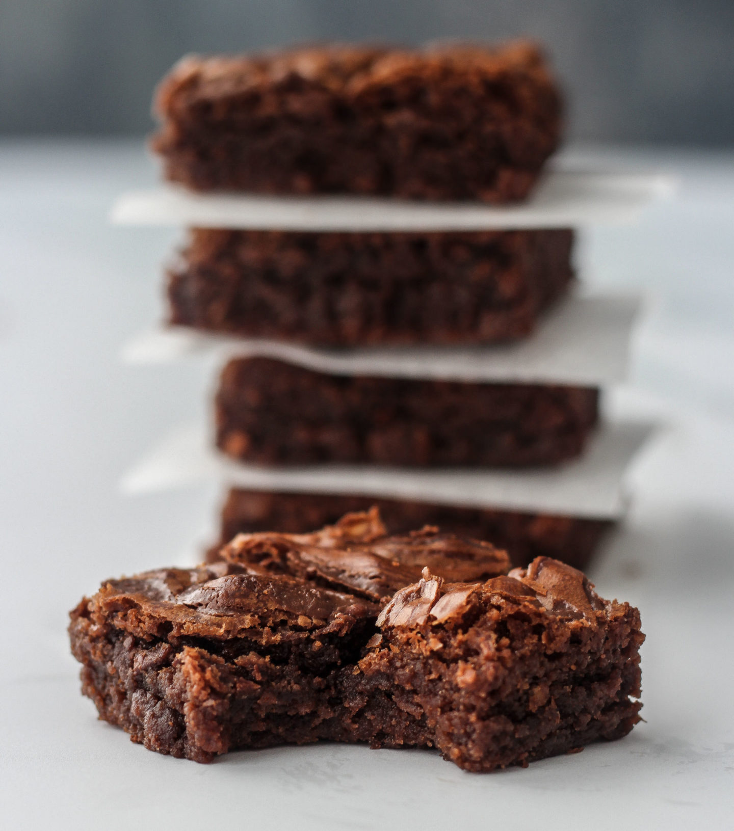 close up of nutella brownie with bite taken out of it and tower of brownies in background