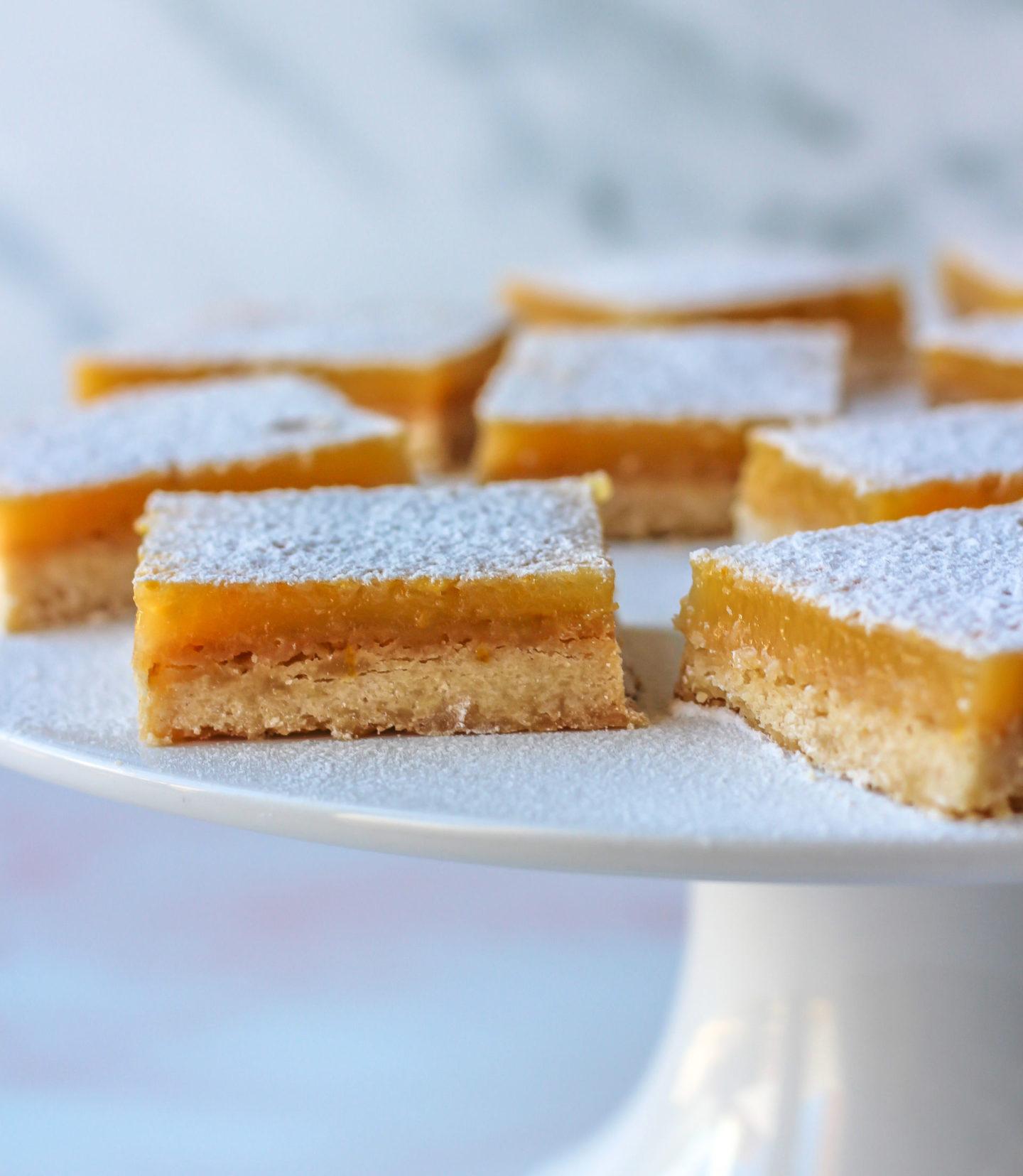 several lemon bars on cake stand