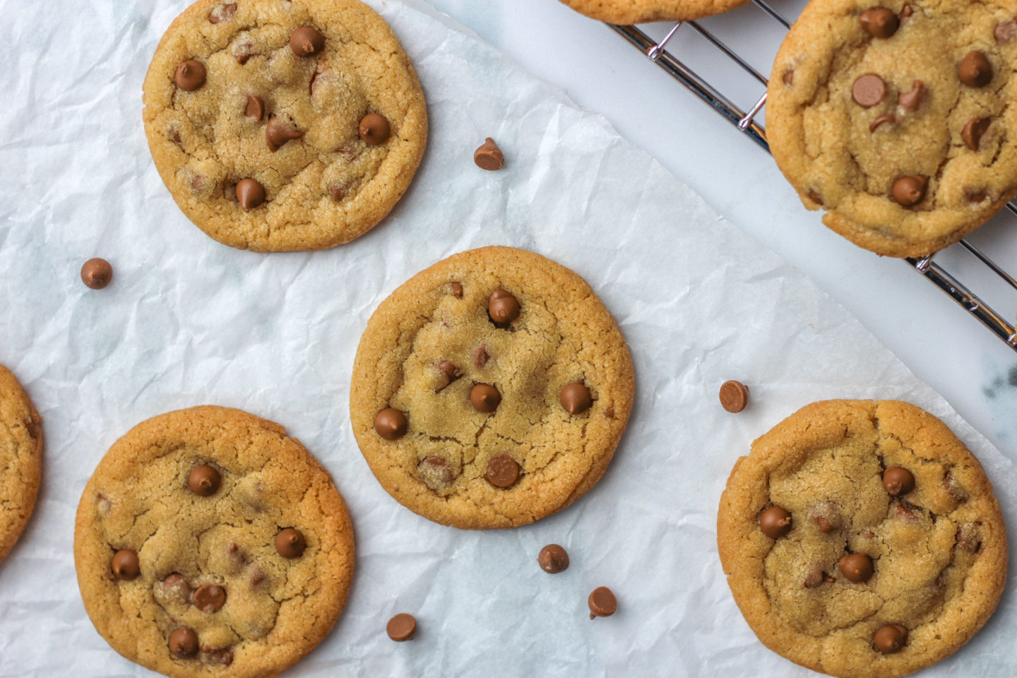 Several chewy chocolate chip cookies on parchment paper on a work surface
