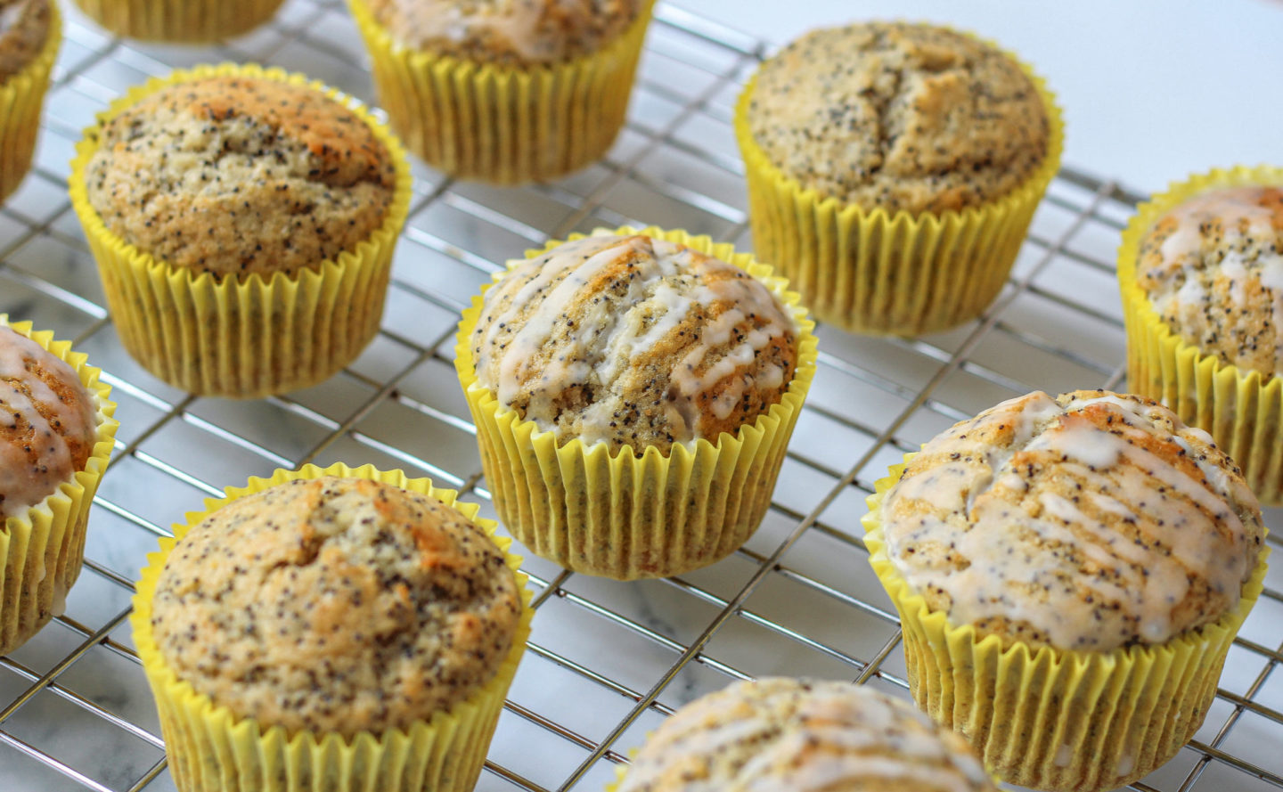 several lemon poppy seed muffins with and without lemon glaze on wire rack