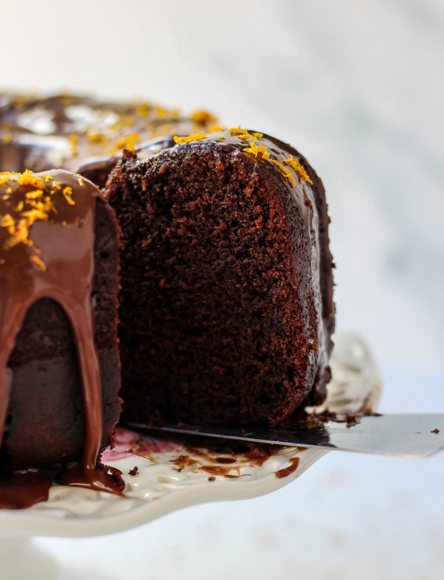 Close up of slice being removed from chocolate orange Bundt cake