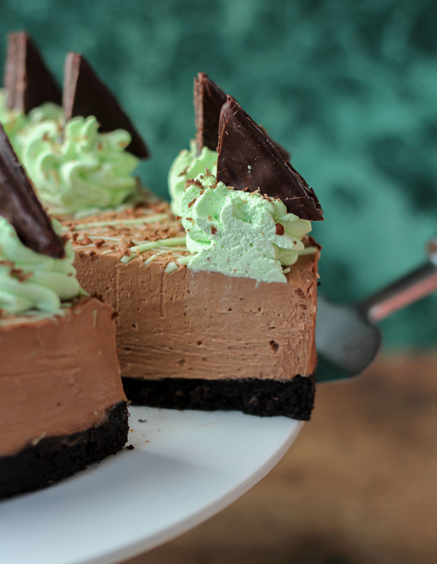 Close up of slice of no-bake mint chocolate cheesecake being removed from serving plate