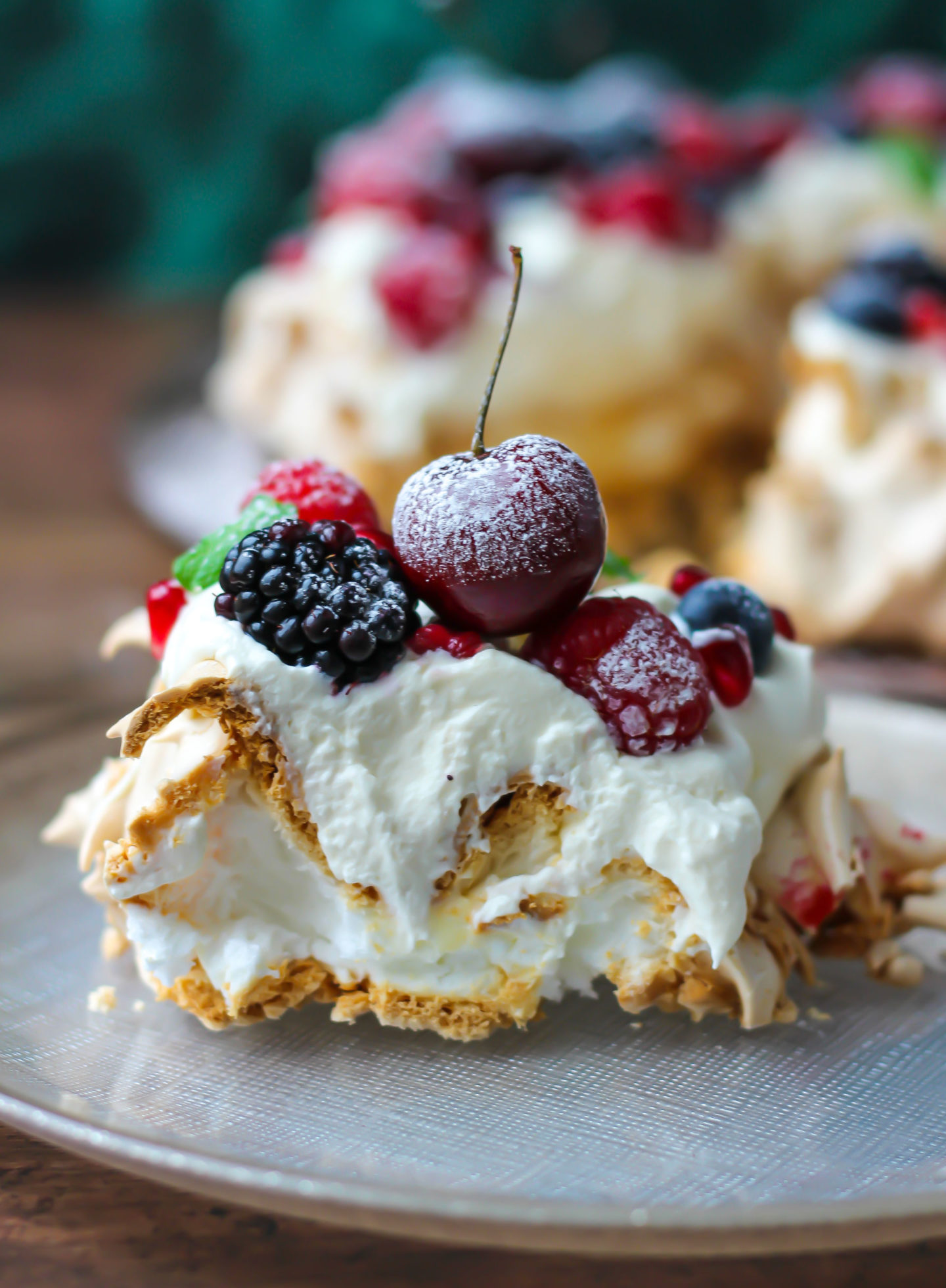 close up side on view of a slice of Christmas berry pavlova wreath