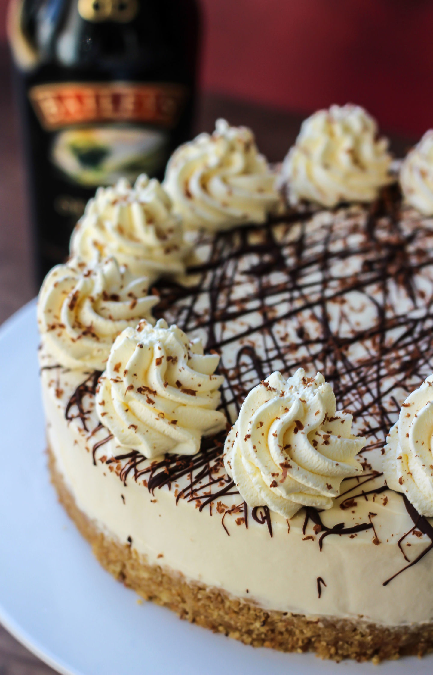close up of no-bake Baileys cheesecake with bottle of Baileys in background