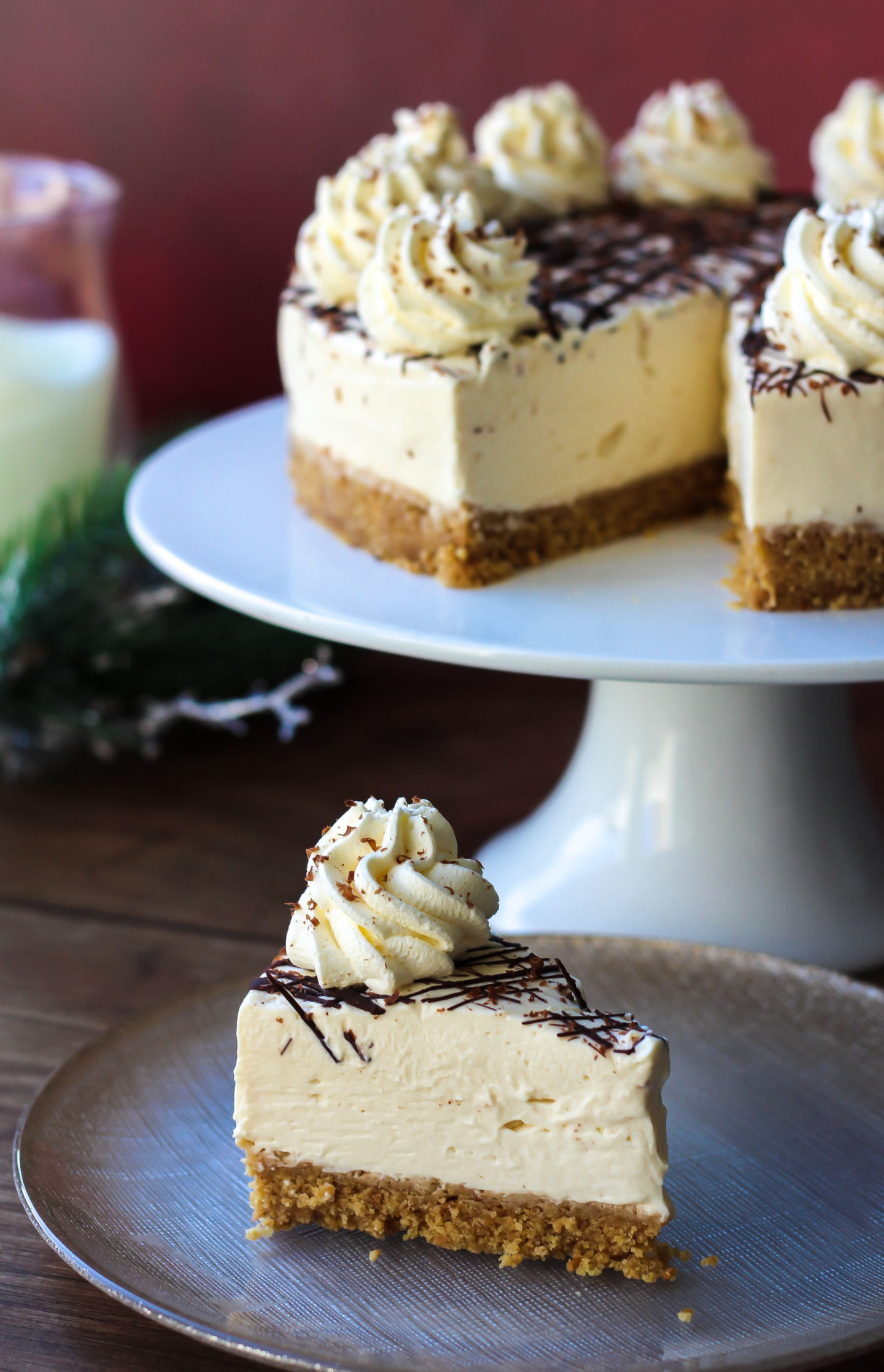 Slice of no-bake Baileys cheesecake with rest of cheesecake on a cake stand in the background