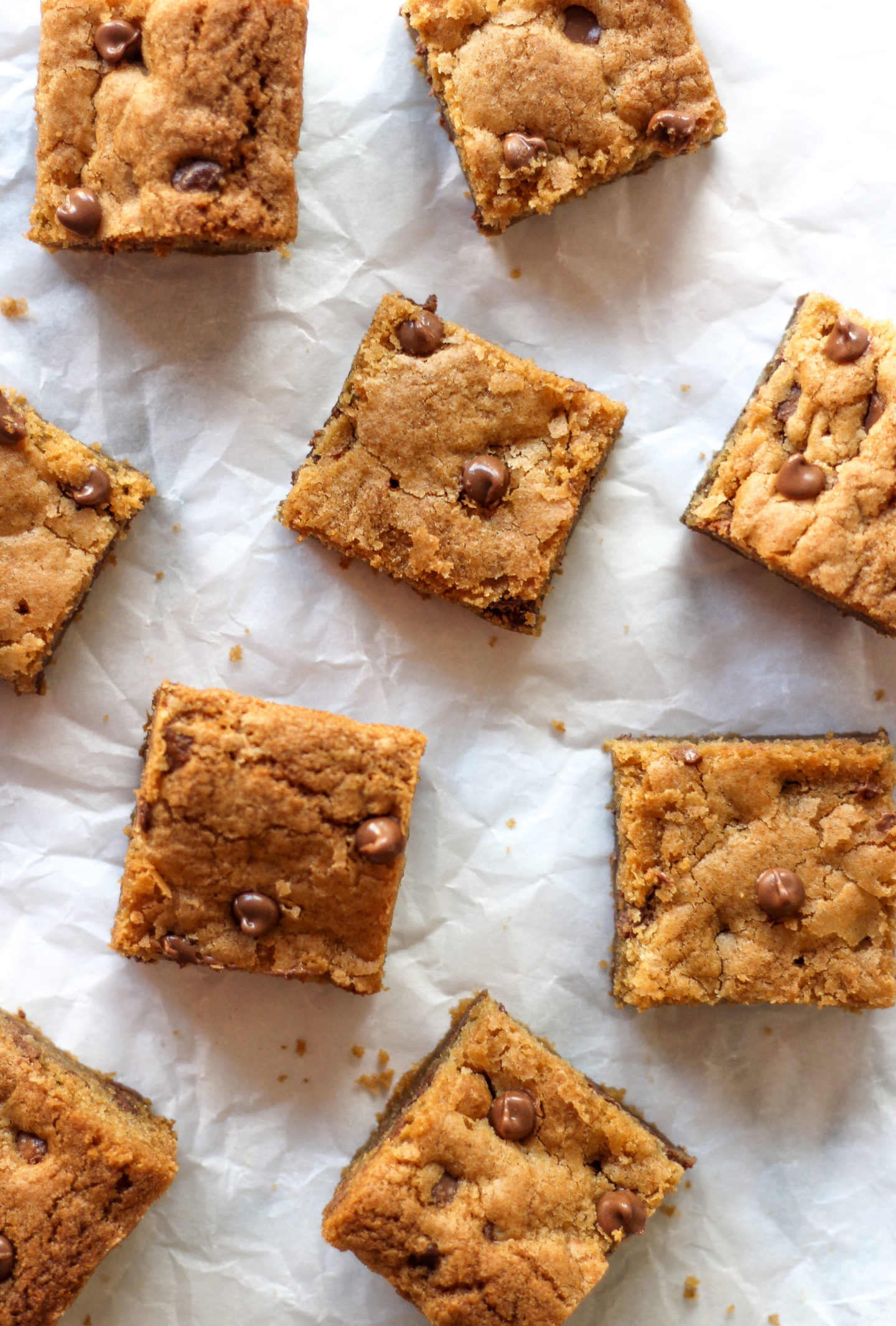 overhead view of chewy chocolate chip cookie bars on parchment paper