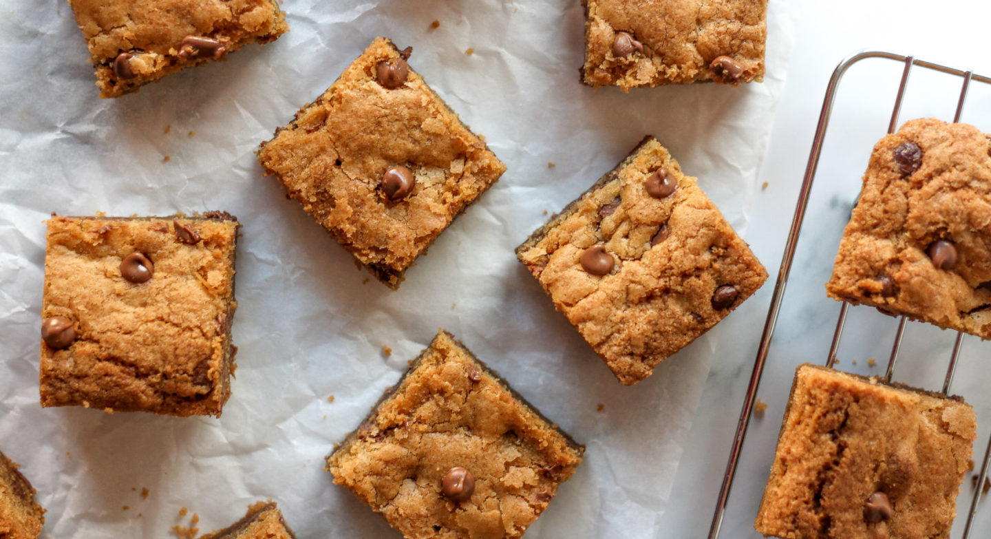overhead view of several chewy chocolate chip cookie bars on parchment paper