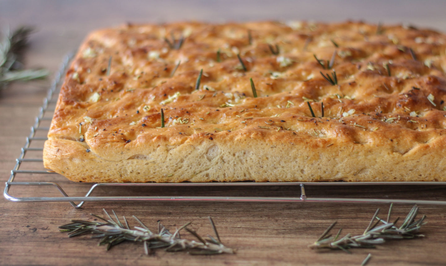 whole garlic and rosemary focaccia on wire rack