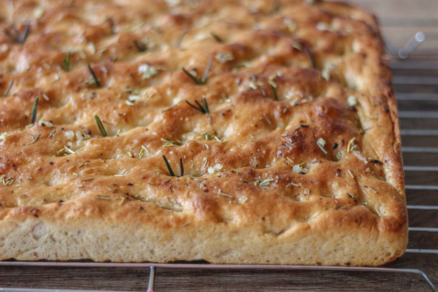 whole garlic and rosemary focaccia on a wire rack