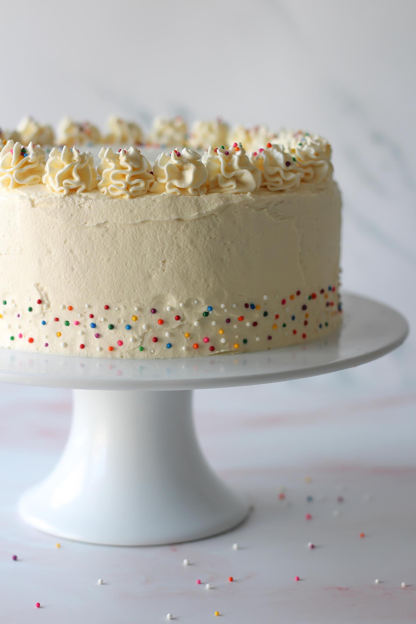 whole vanilla layer cake with vanilla buttercream on a white cakestand