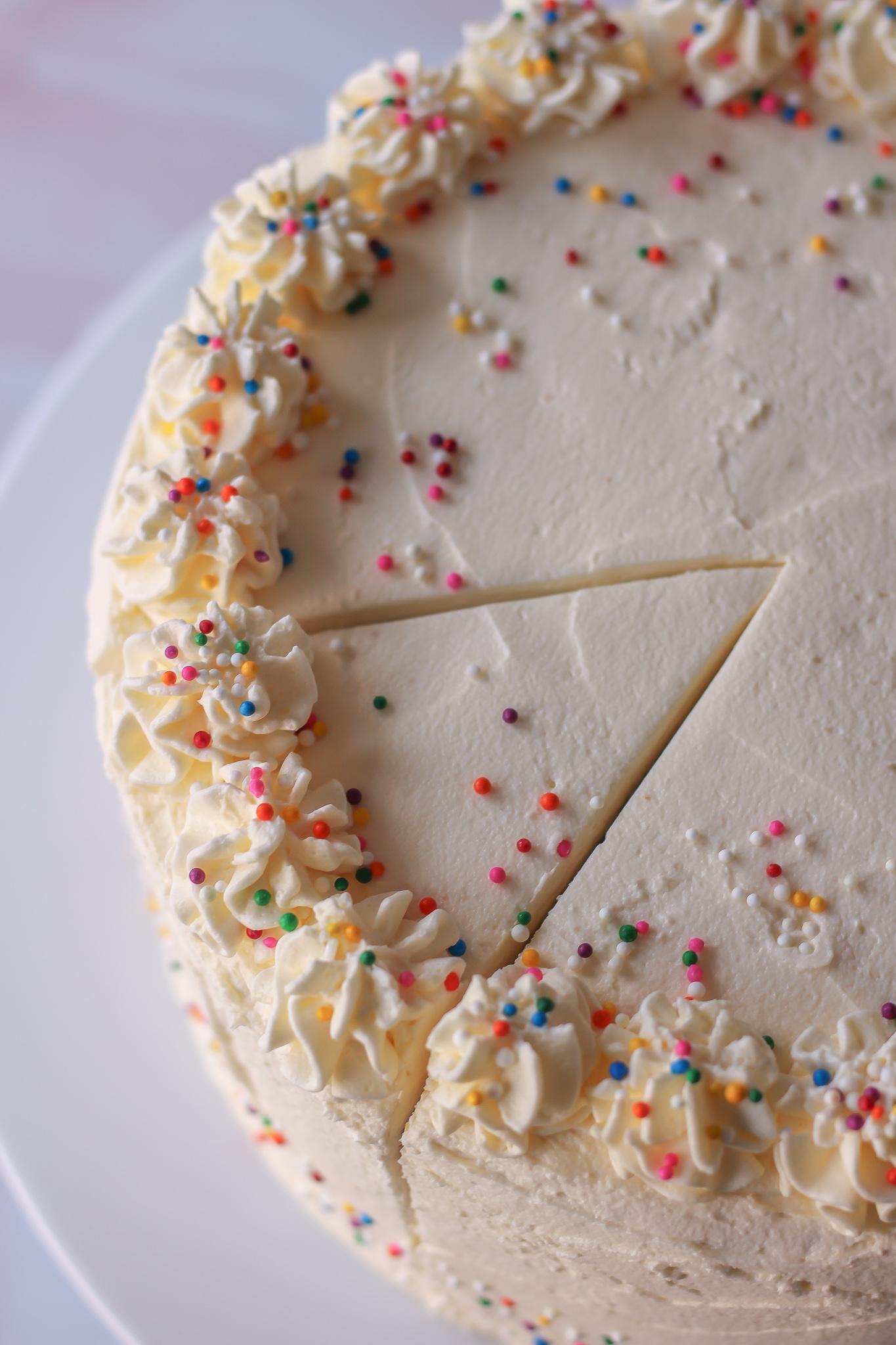 sliced vanilla layer cake with vanilla buttercream, where slice hasn't been removed yet