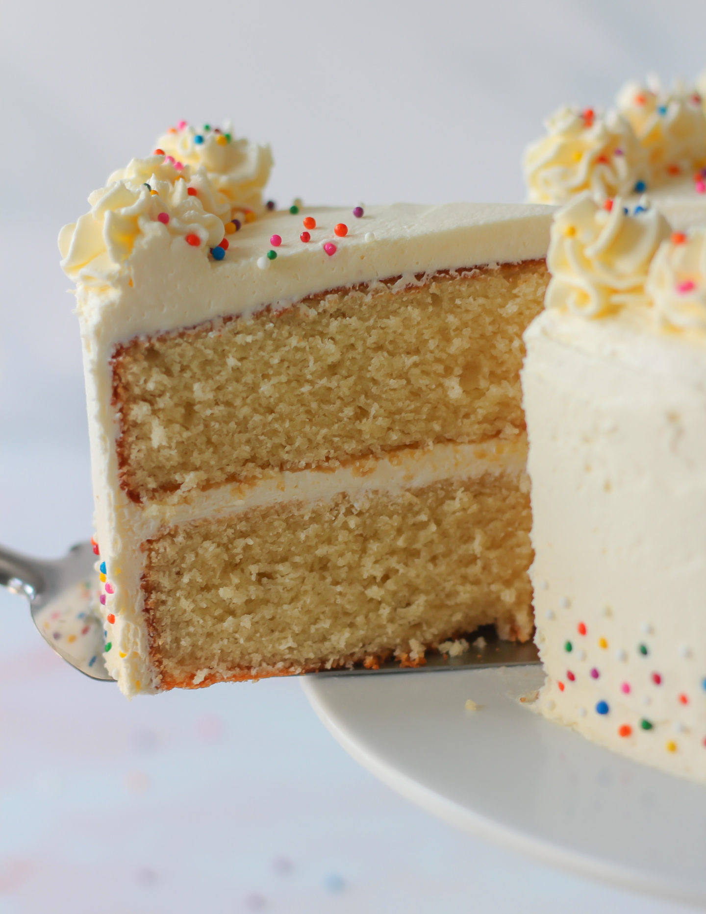 slice of cake being removed from vanilla layer cake with vanilla buttercream