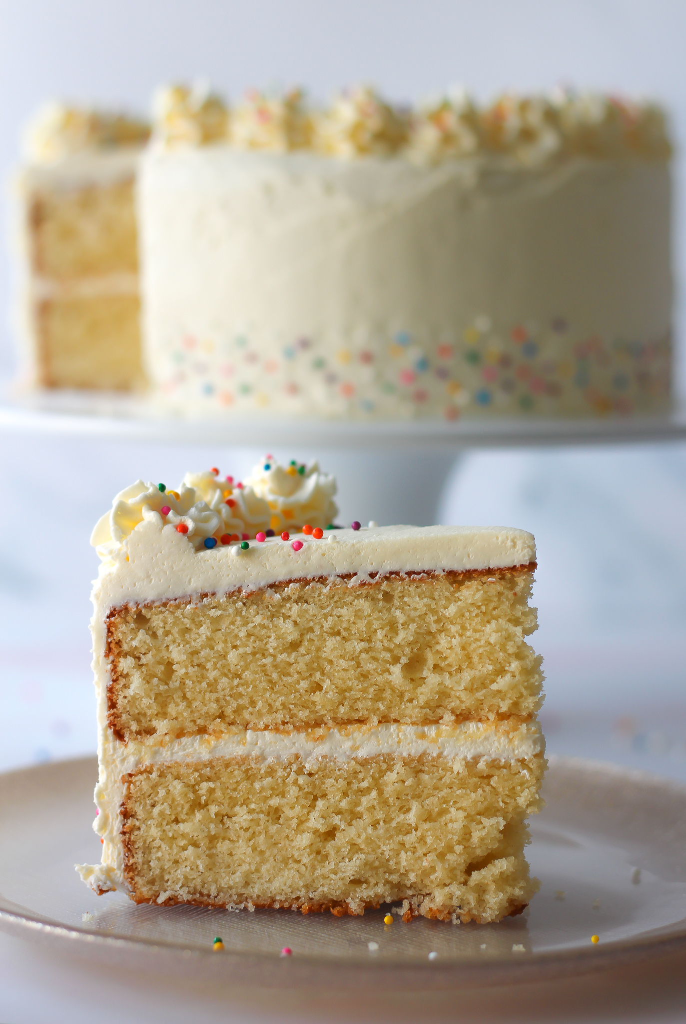 close up of slice of vanilla layer cake with vanilla buttercream with the rest of the cake on a cake stand in the background