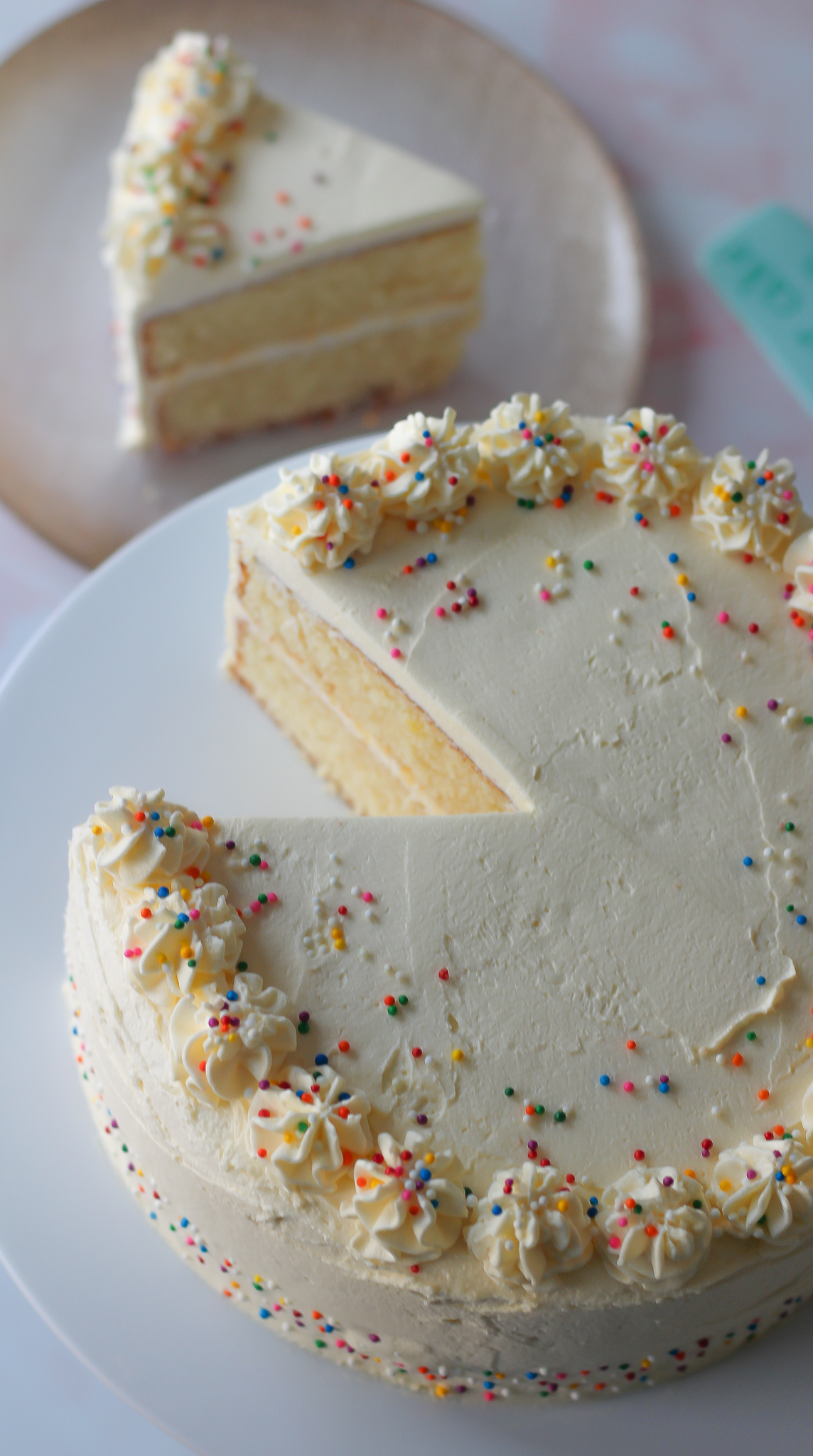 view from above of sliced vanilla layer cake with vanilla buttercream, with slice of cake on a plate in the background