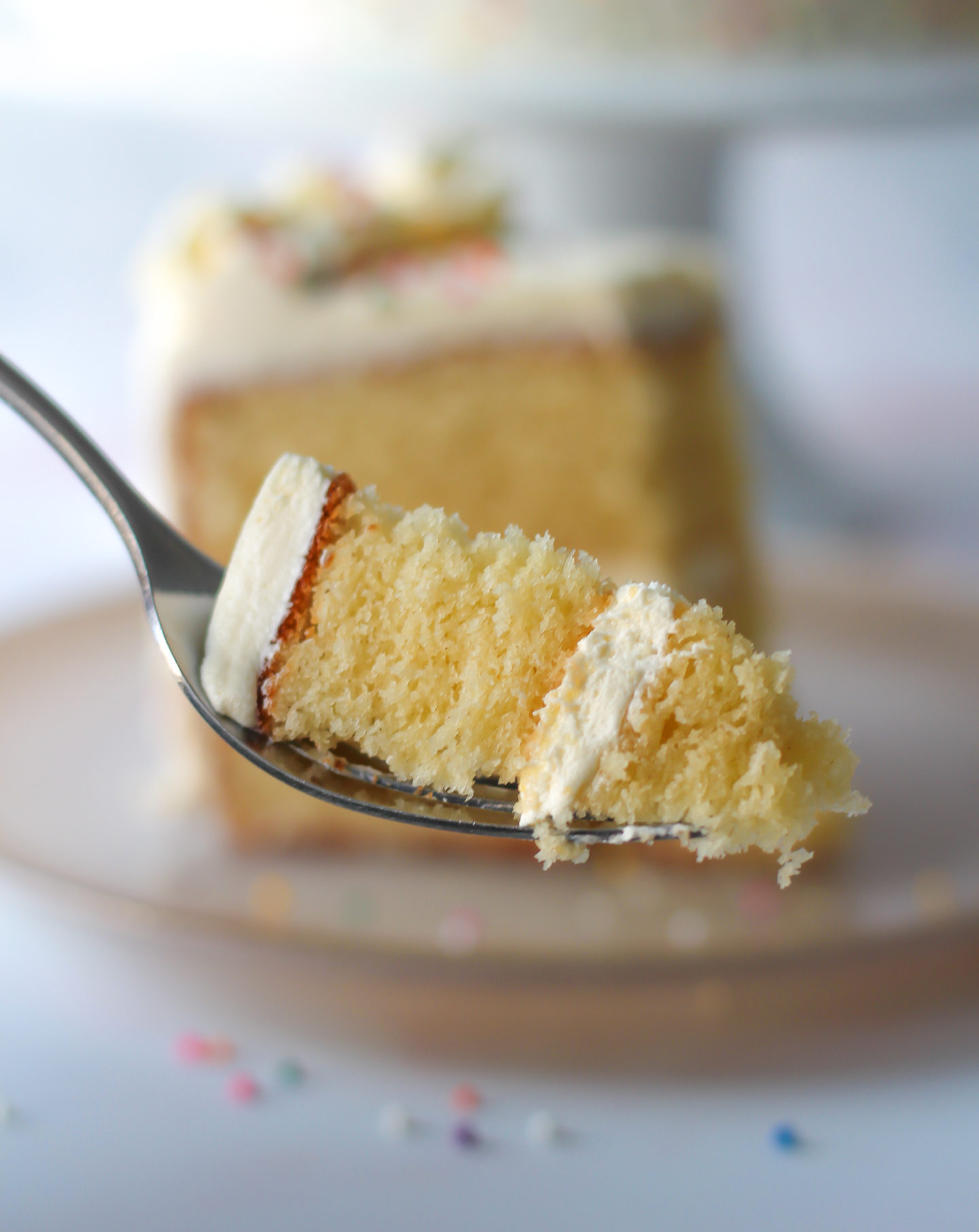 close up of piece of vanilla layer cake with vanilla buttercream on a fork