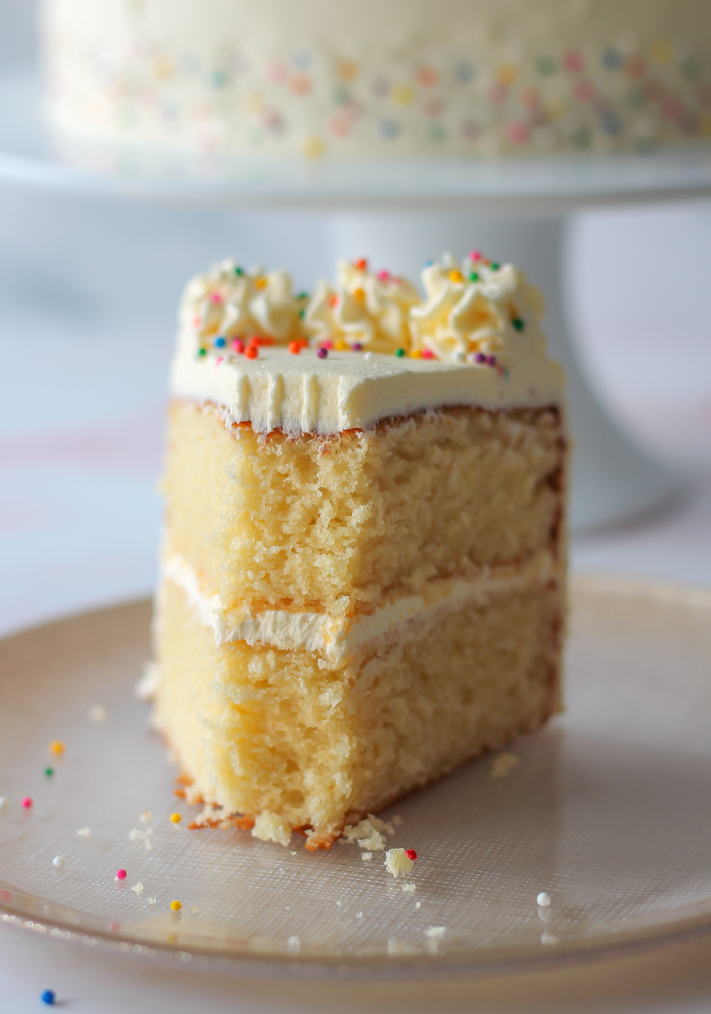 close up of slice of vanilla layer cake with vanilla buttercream where a small part of the cake has been removed with a fork