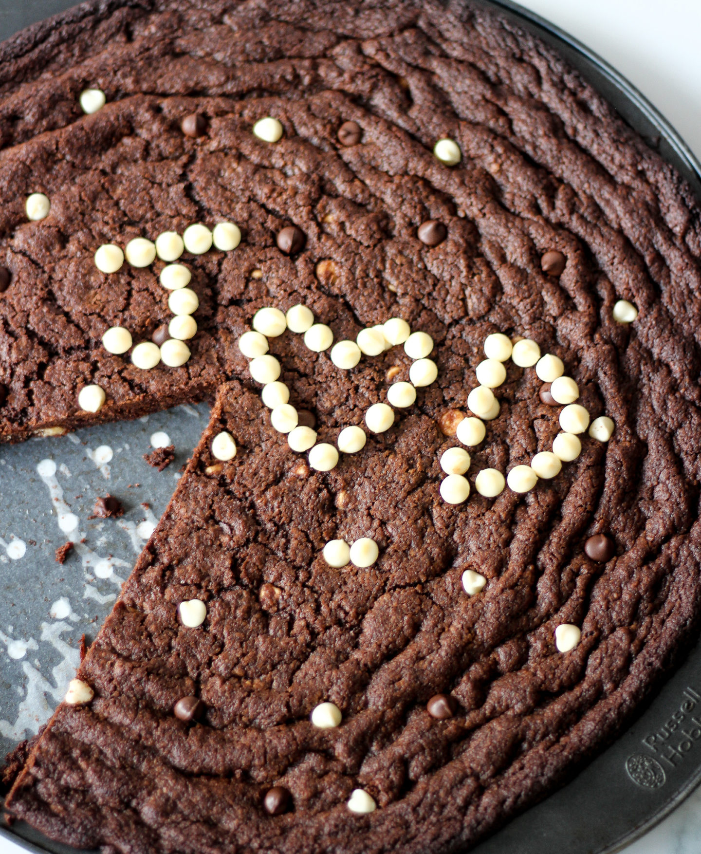 sliced triple chocolate chip cookie pizza with white chocolate chip initials to decorate