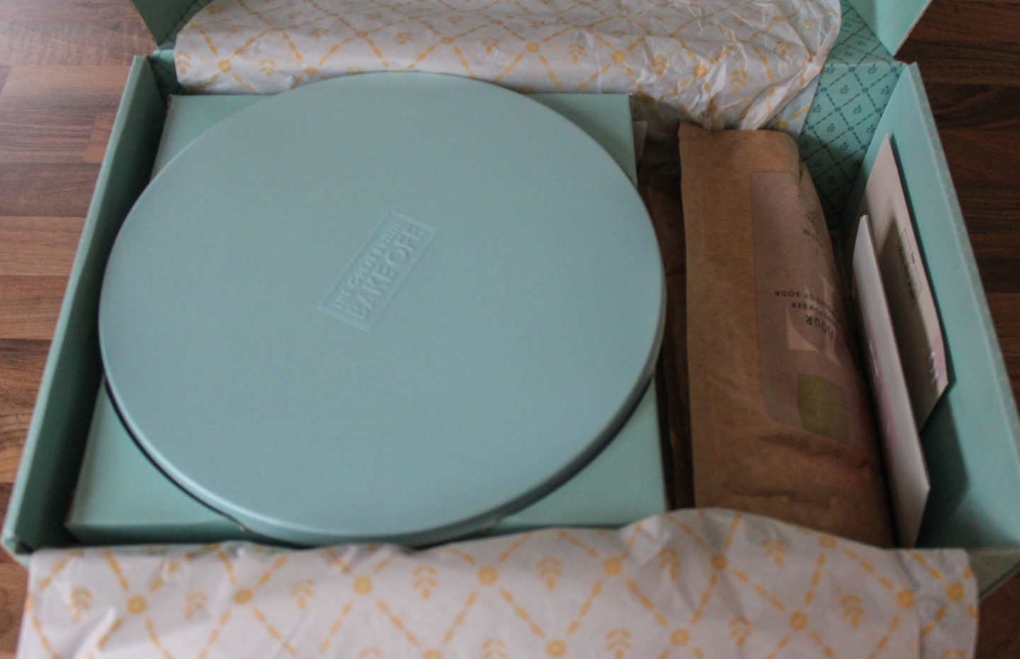 Inside of Bake Off Box showing the cake stand, bags of dry ingredients and recipe card
