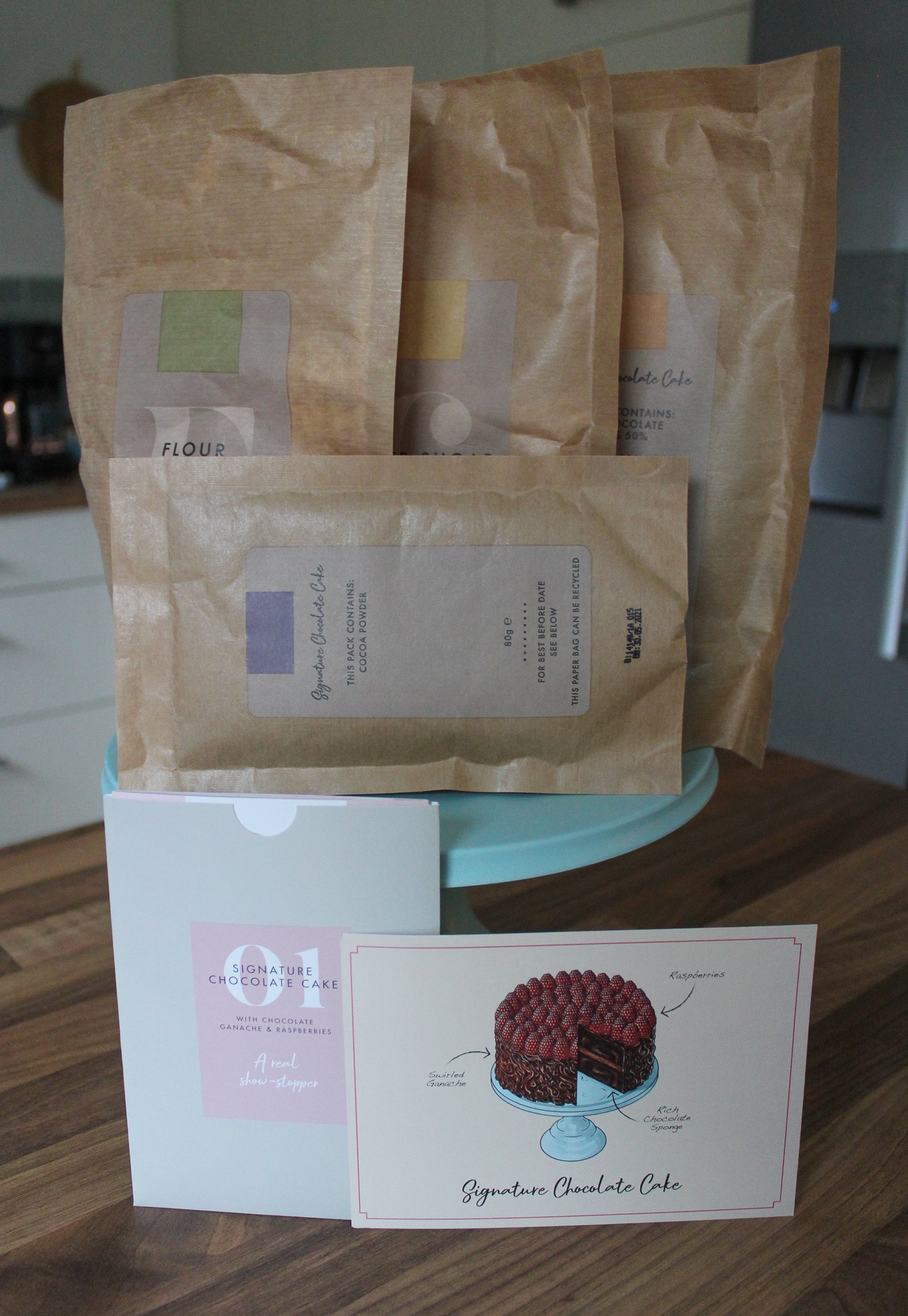 All of the pre-measured dry ingredients in unopened bags, sat on top of the blue bamboo cake stand, with recipe card at front.