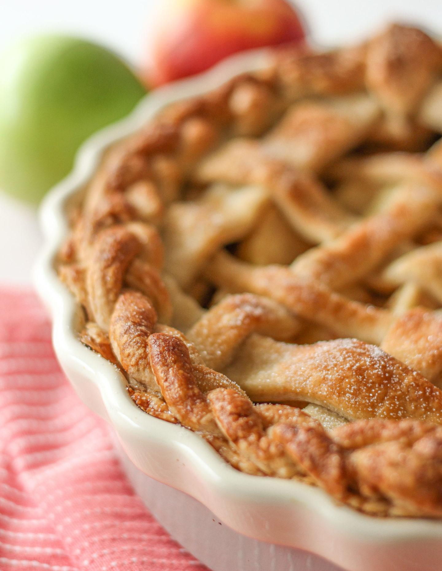 close up of unsliced lattice apple pie, focussed on the plaited crust