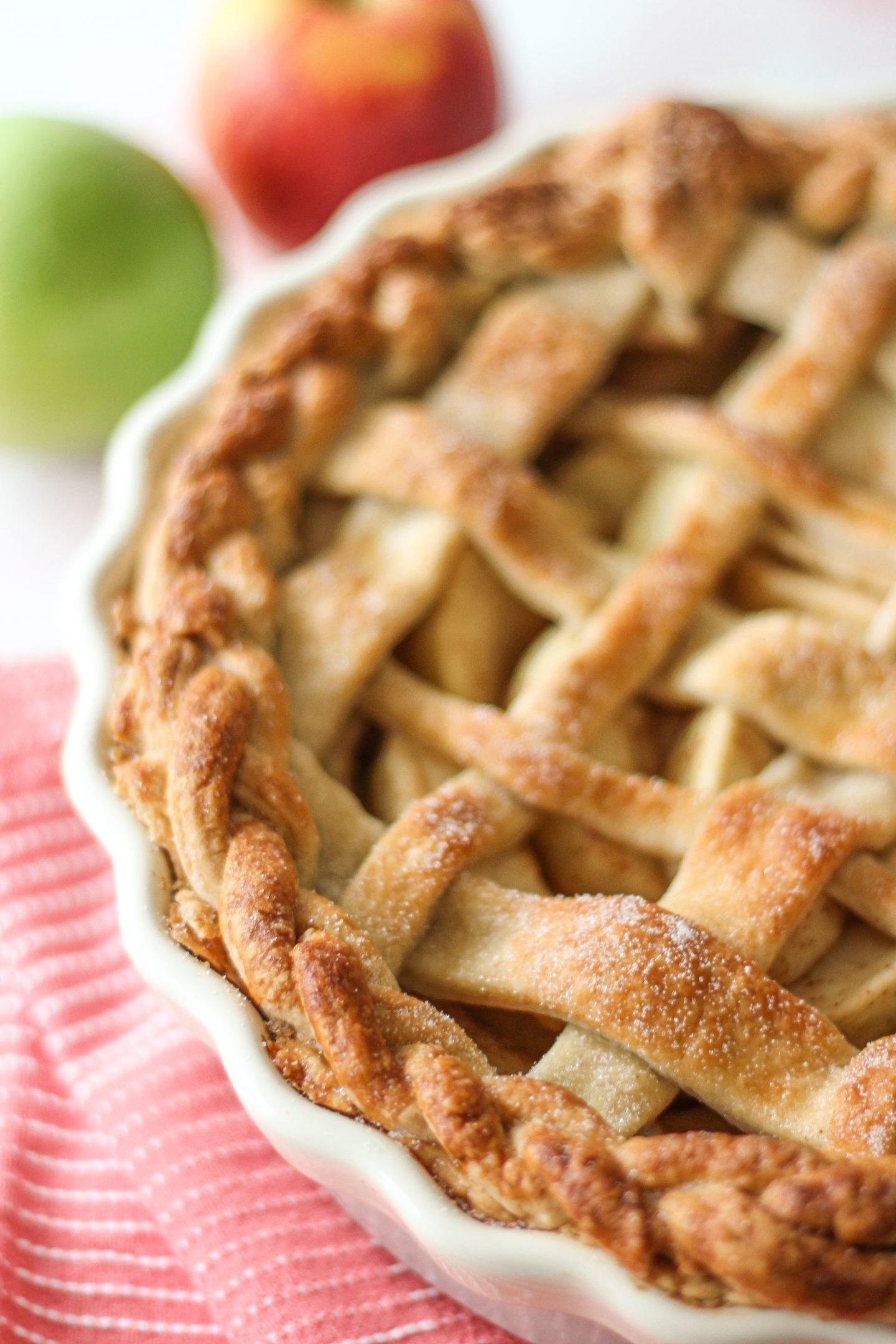 close up of lattice apple pie in pie dish, focussed on outer plaited crust