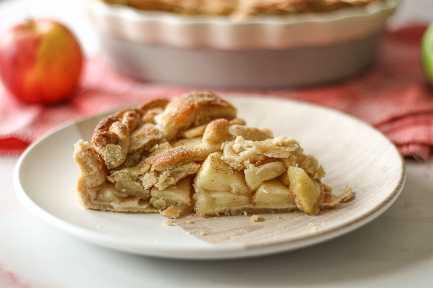 close up of slice of lattice apple pie with pie dish blurred in background