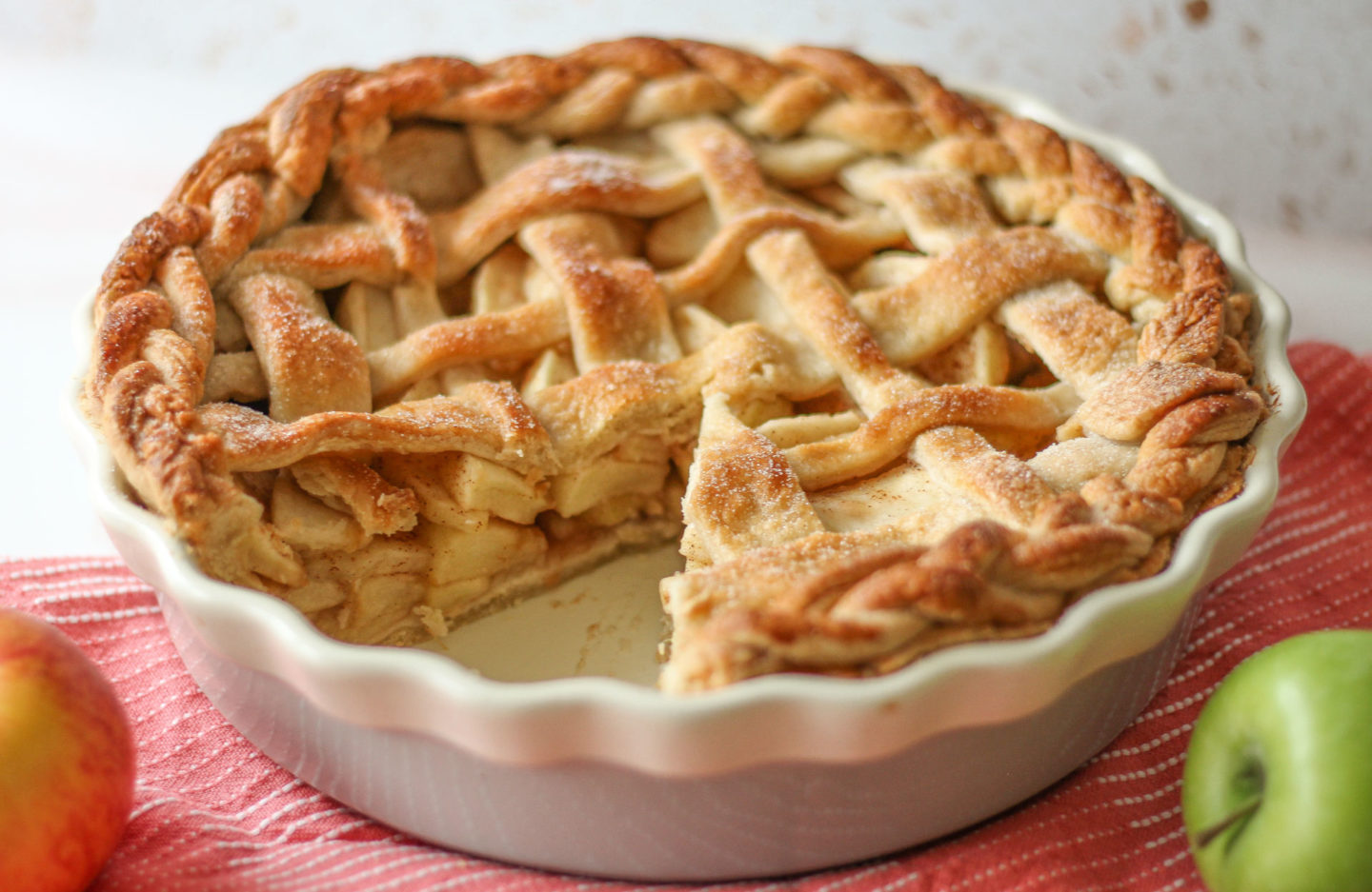 whole lattice apple pie with slice taken from it, showing the filling inside