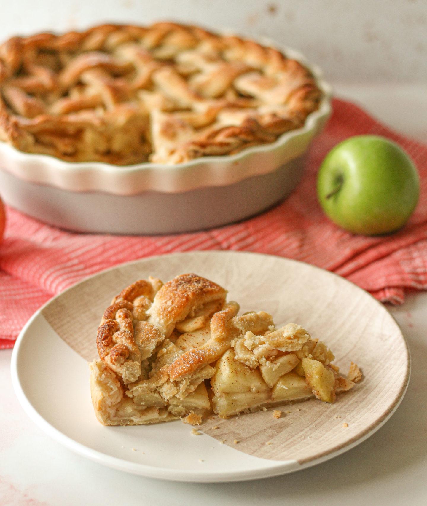Slice of lattice apple pie with whole lattice apple pie blurred in background