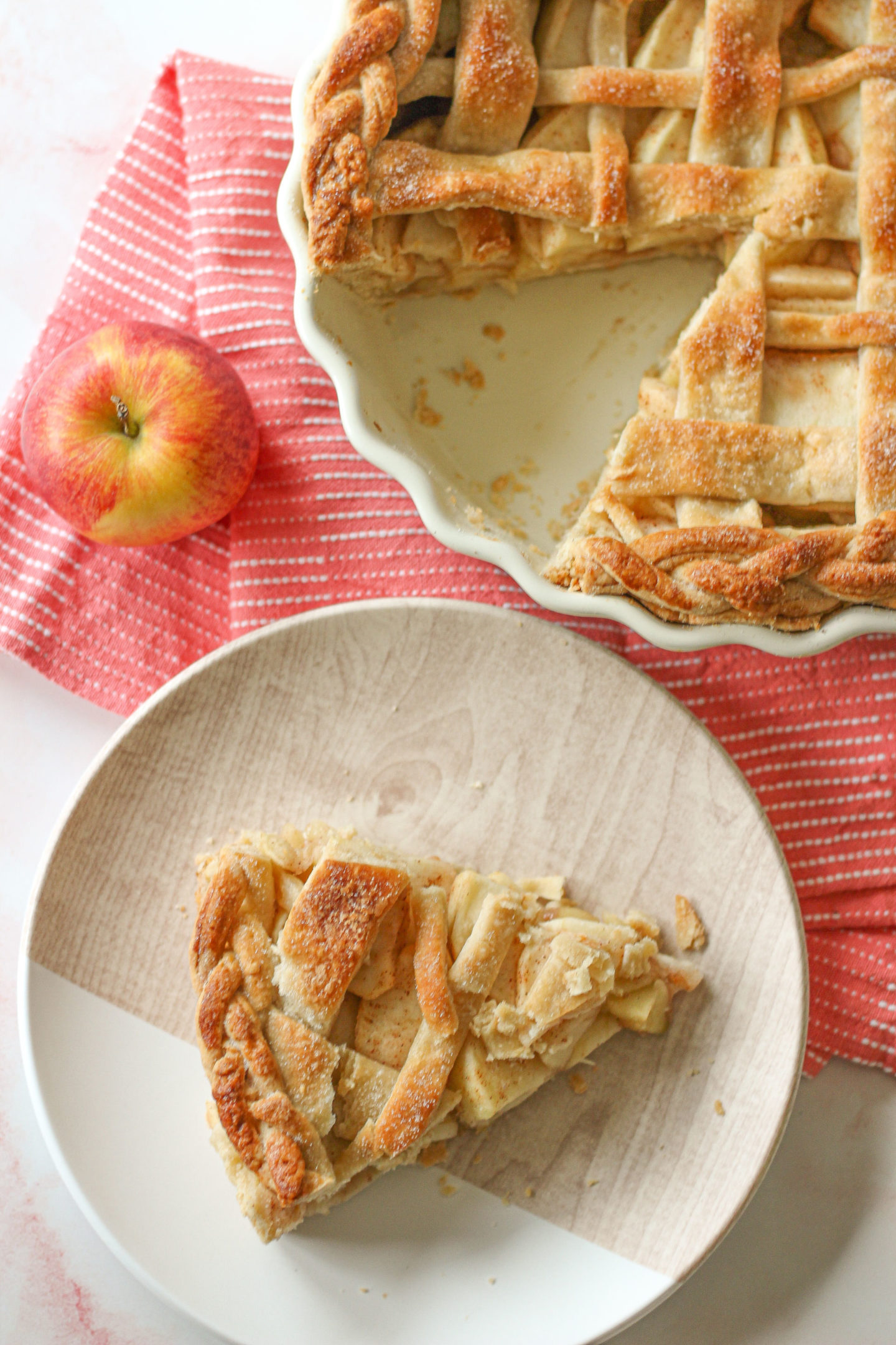 overhead view of a slice of lattice apple pie with part of the pie in the pie dish shown above it