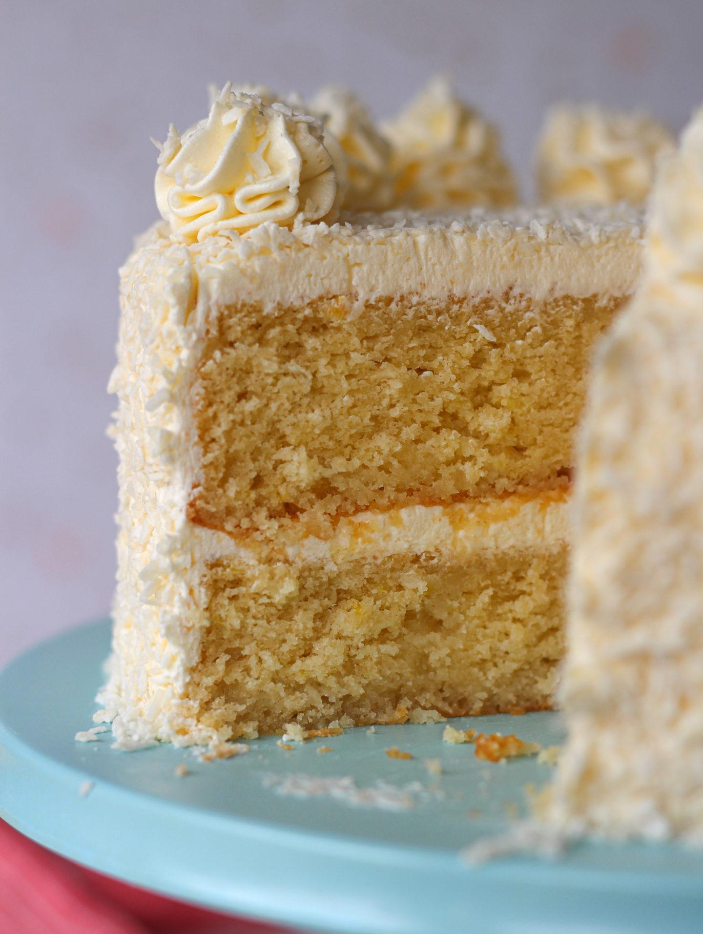 close up inside sliced lemon coconut layer cake on blue cake stand