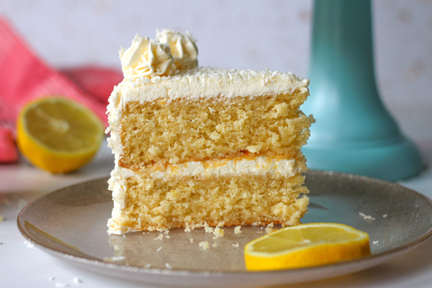 close up of a slice of lemon coconut layer cake on a small plate