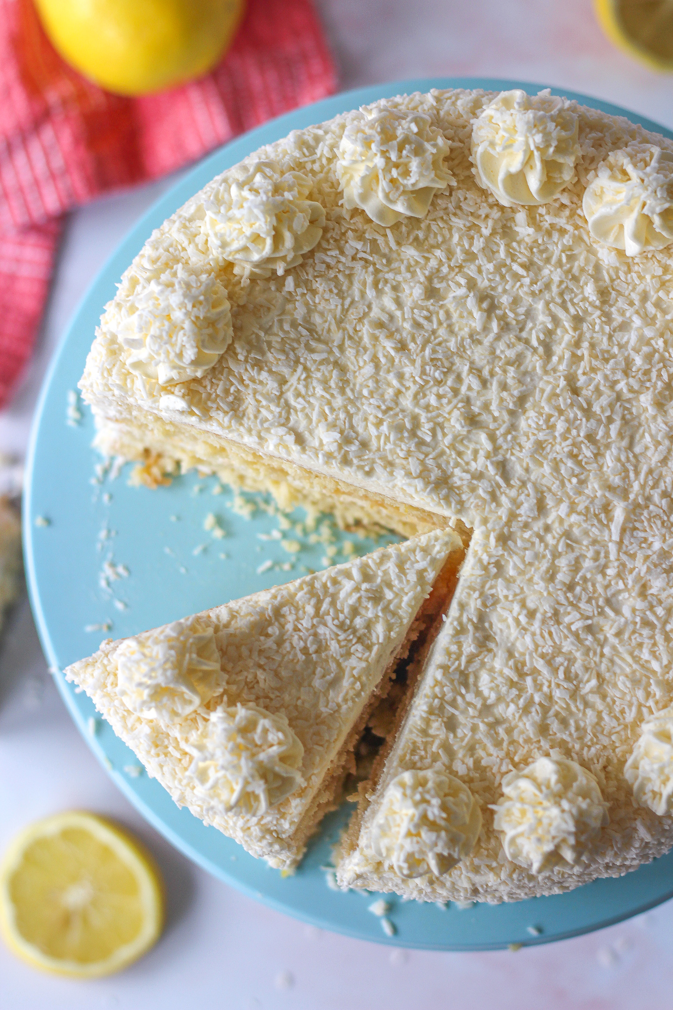view from above of partly sliced lemon coconut layer cake