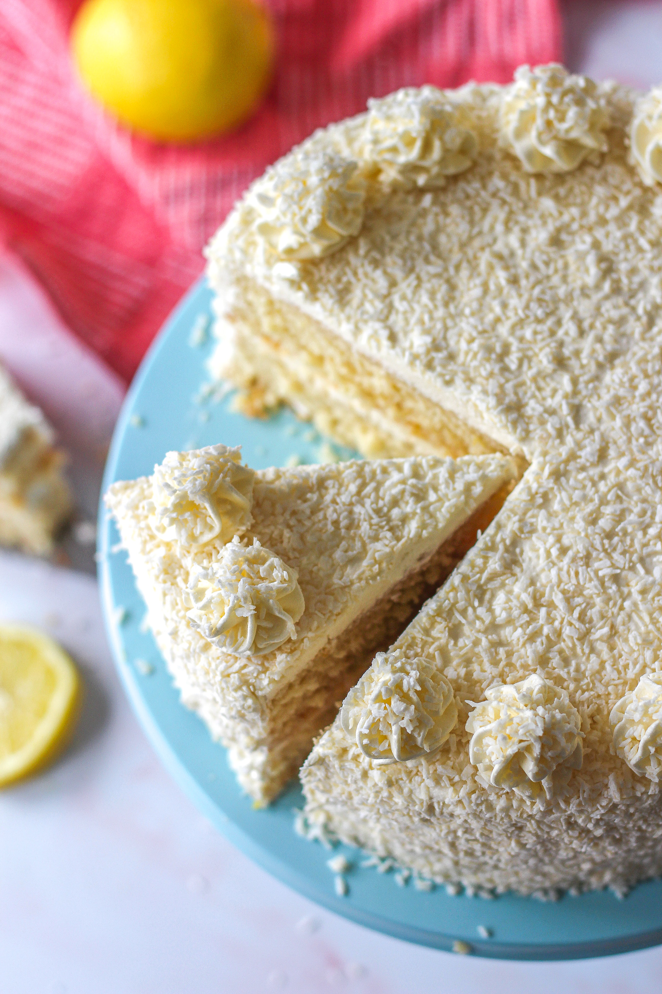 view from above of lemon coconut layer cake slice adjacent to rest of cake