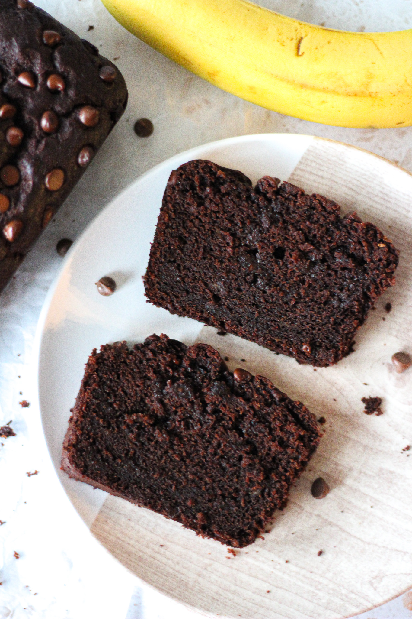 overhead view of two slices of chocolate banana loaf cake on a small plate