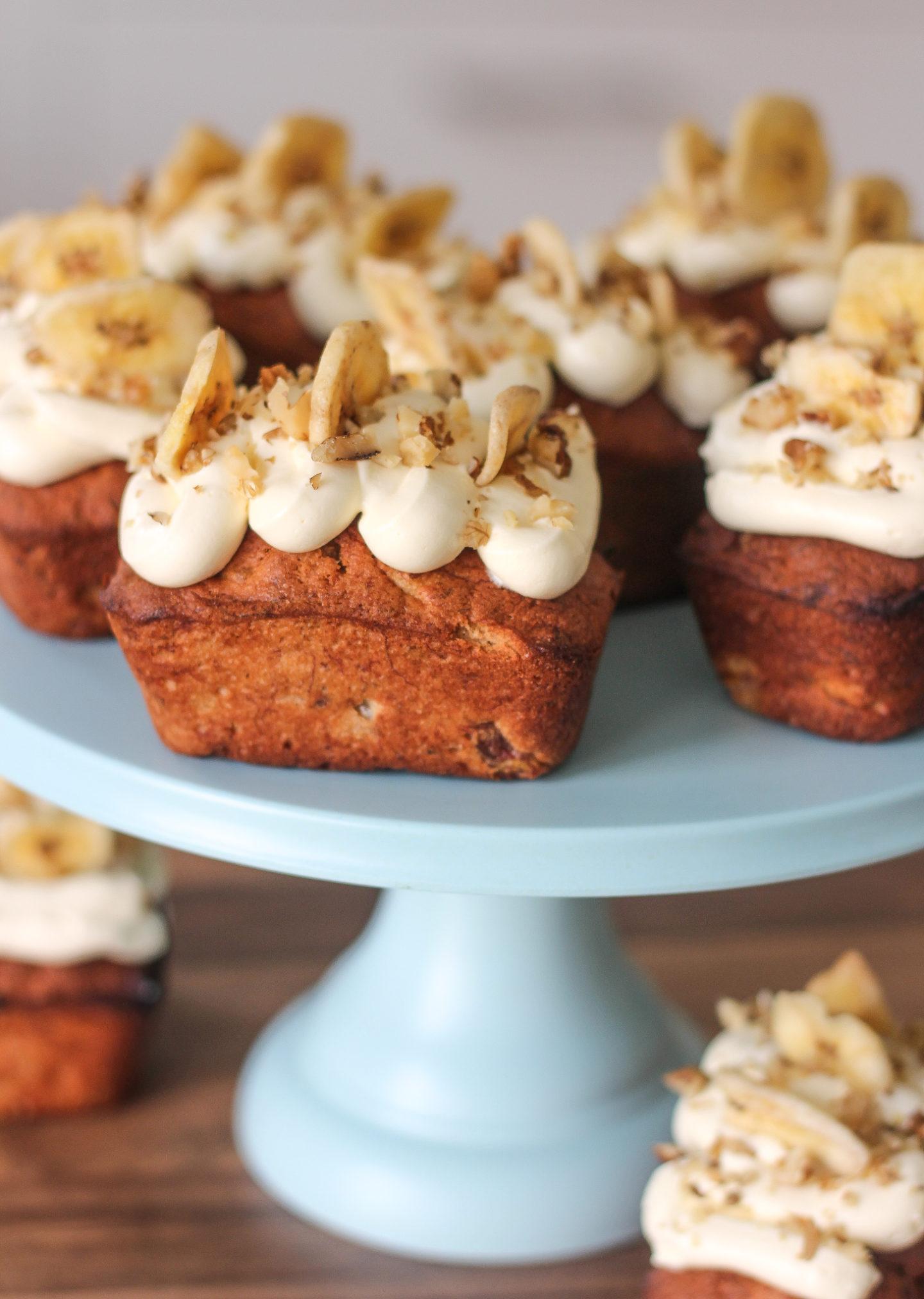 several banana and walnut mini loaves on a blue cake stand