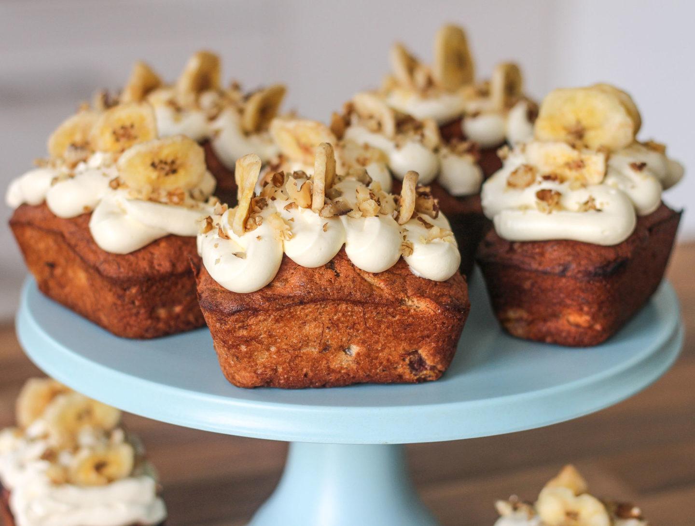 several banana and walnut mini loaves on blue cake stand