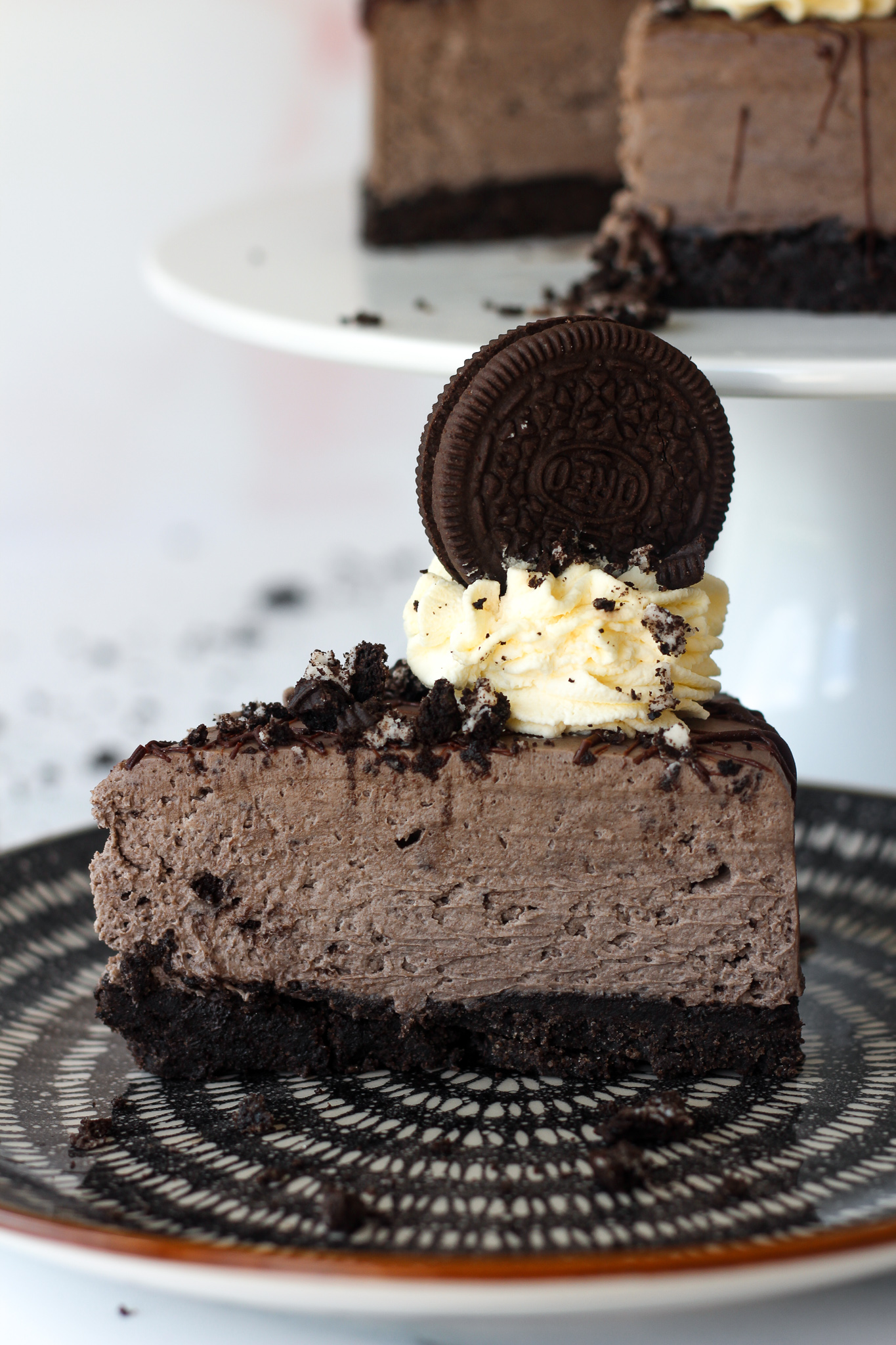 close up of a slice of no-bake Oreo cheesecake on a serving plate