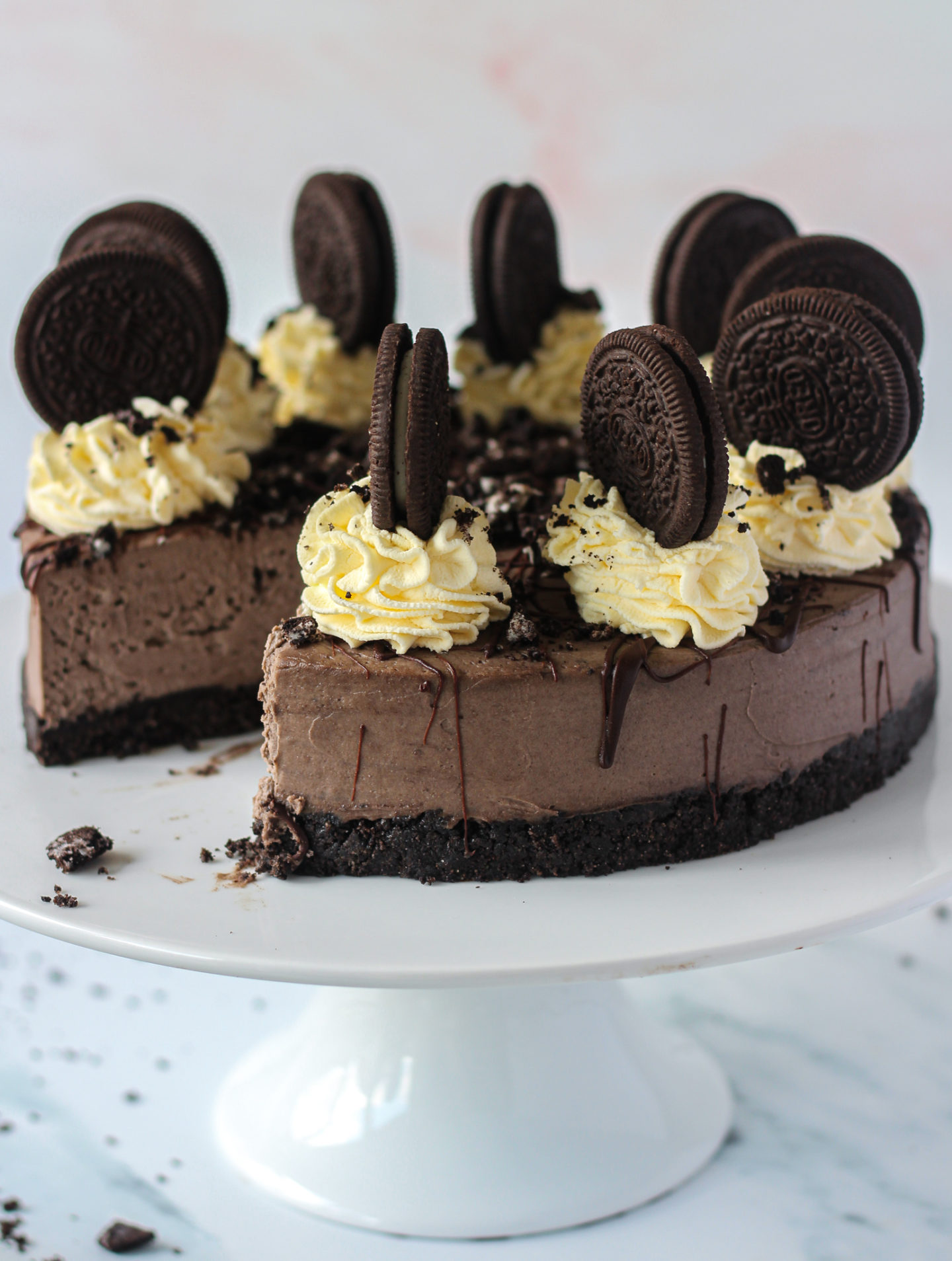 no-bake Oreo cheesecake on cake stand with slice missing
